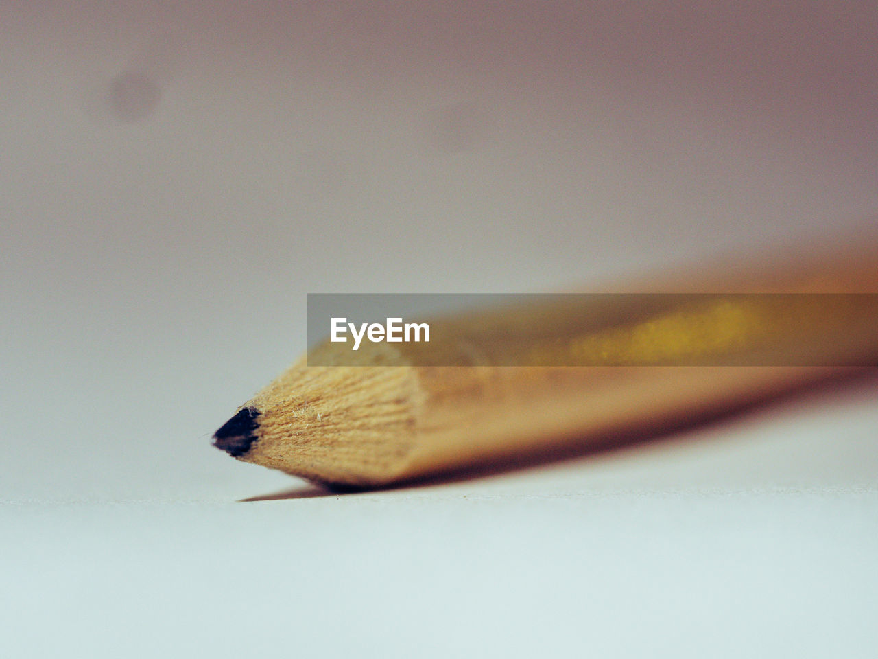 close-up, pencil, no people, still life, single object, selective focus, writing instrument, indoors, wood - material, table, education, focus on foreground, studio shot, copy space, white background, white color, high angle view, brown, simplicity, art and craft, nib