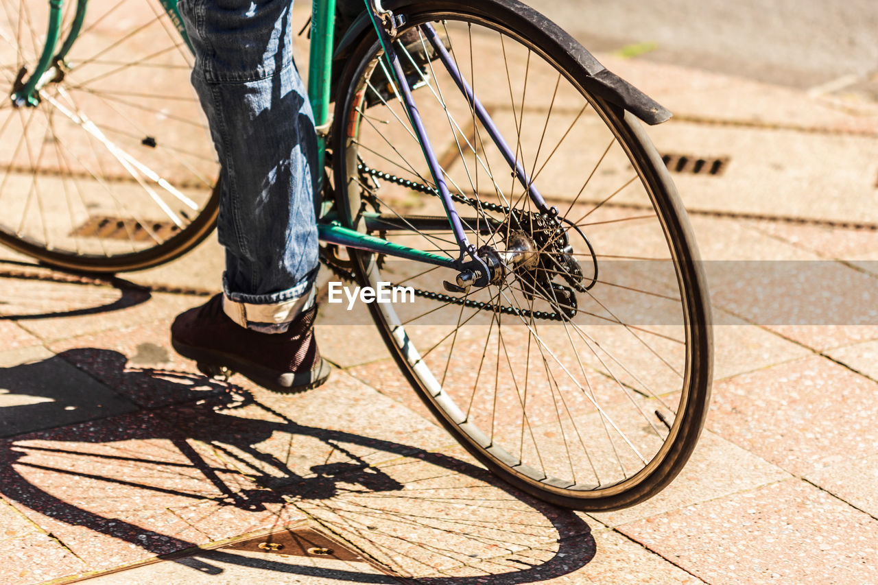 Low Section Of Person Riding Bicycle During Sunny Day