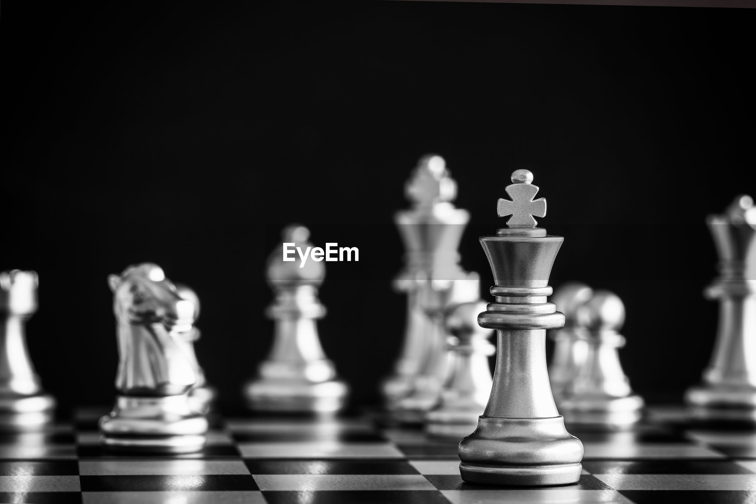 Close-up of chess pieces on board against black background
