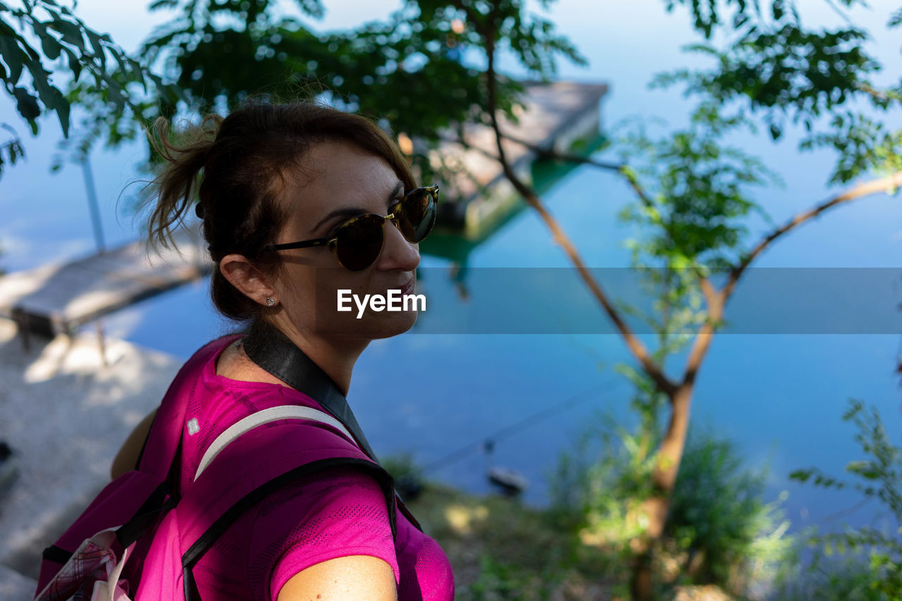 Side view of mid adult woman wearing sunglasses against lake