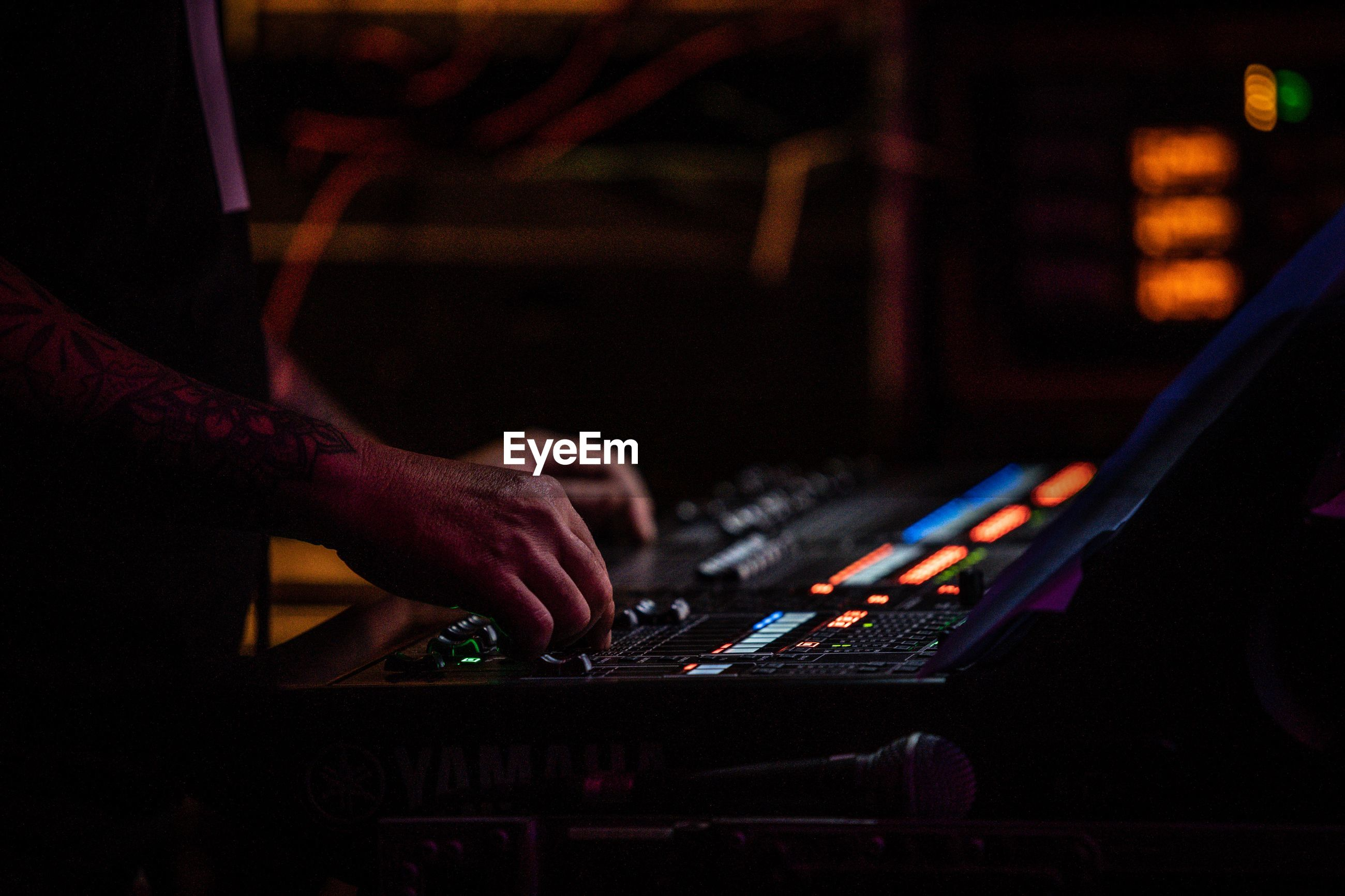 Cropped hands of musician adjusting sound mixer in nightclub