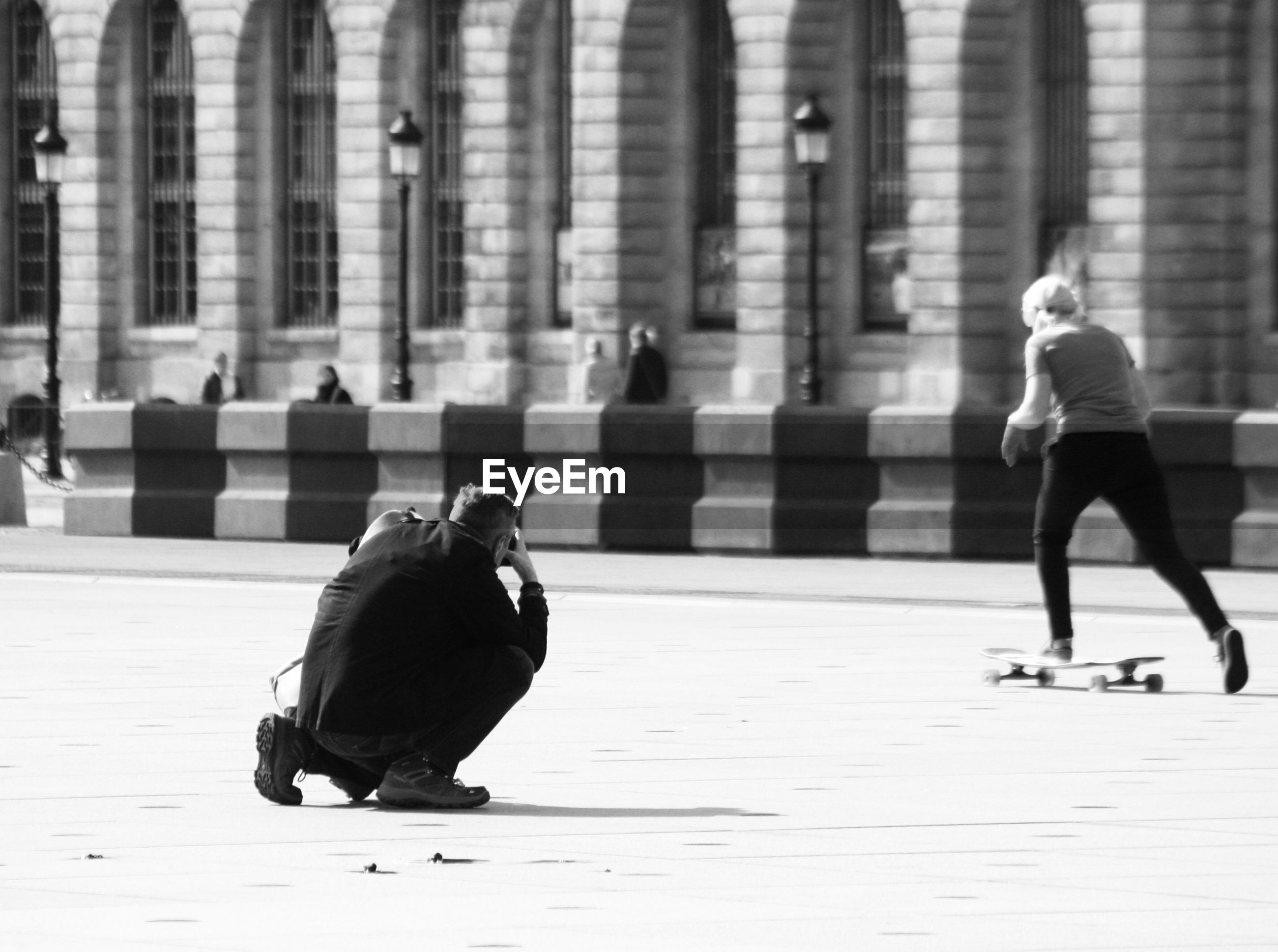 Man photographing while woman skateboarding in city