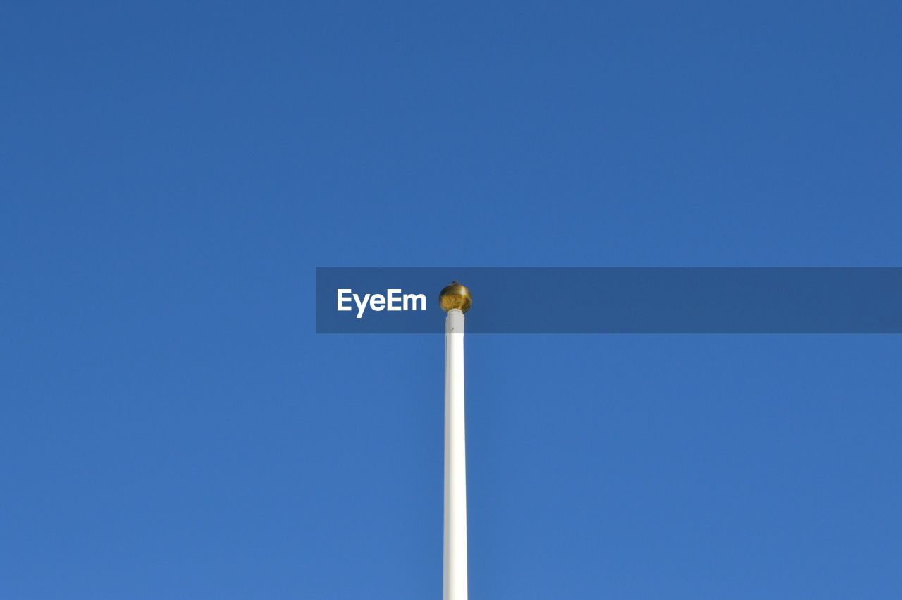 Low angle view of pole against clear blue sky