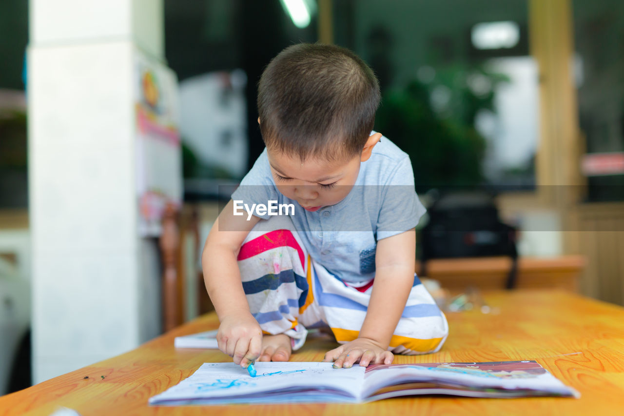 Boy Drawing On Book At Table