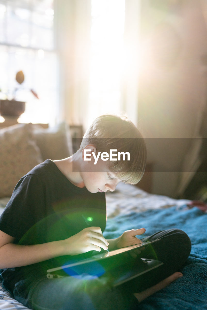 REAR VIEW OF BOY LOOKING AT CAMERA