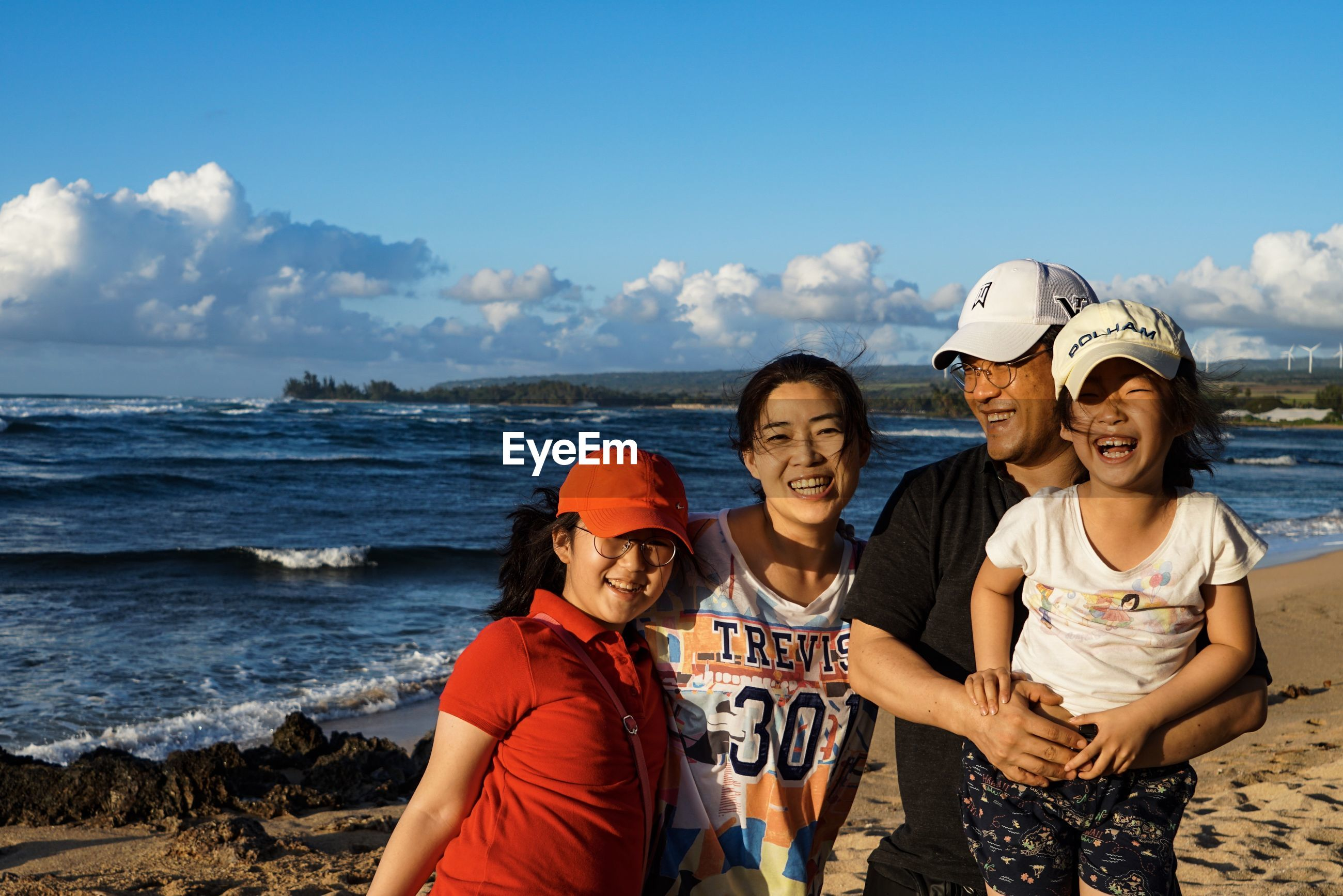 PORTRAIT OF SMILING FRIENDS ON BEACH AGAINST SEA AGAINST SKY