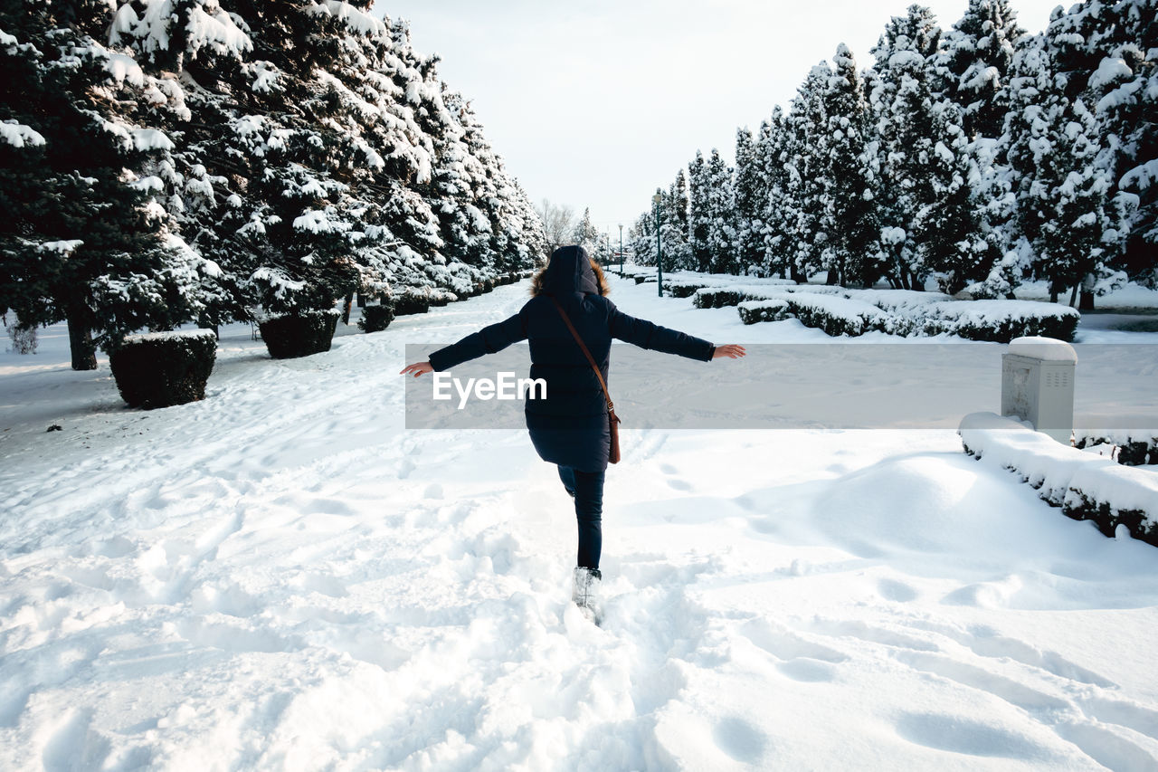 Rear view of woman walking on snow covered land