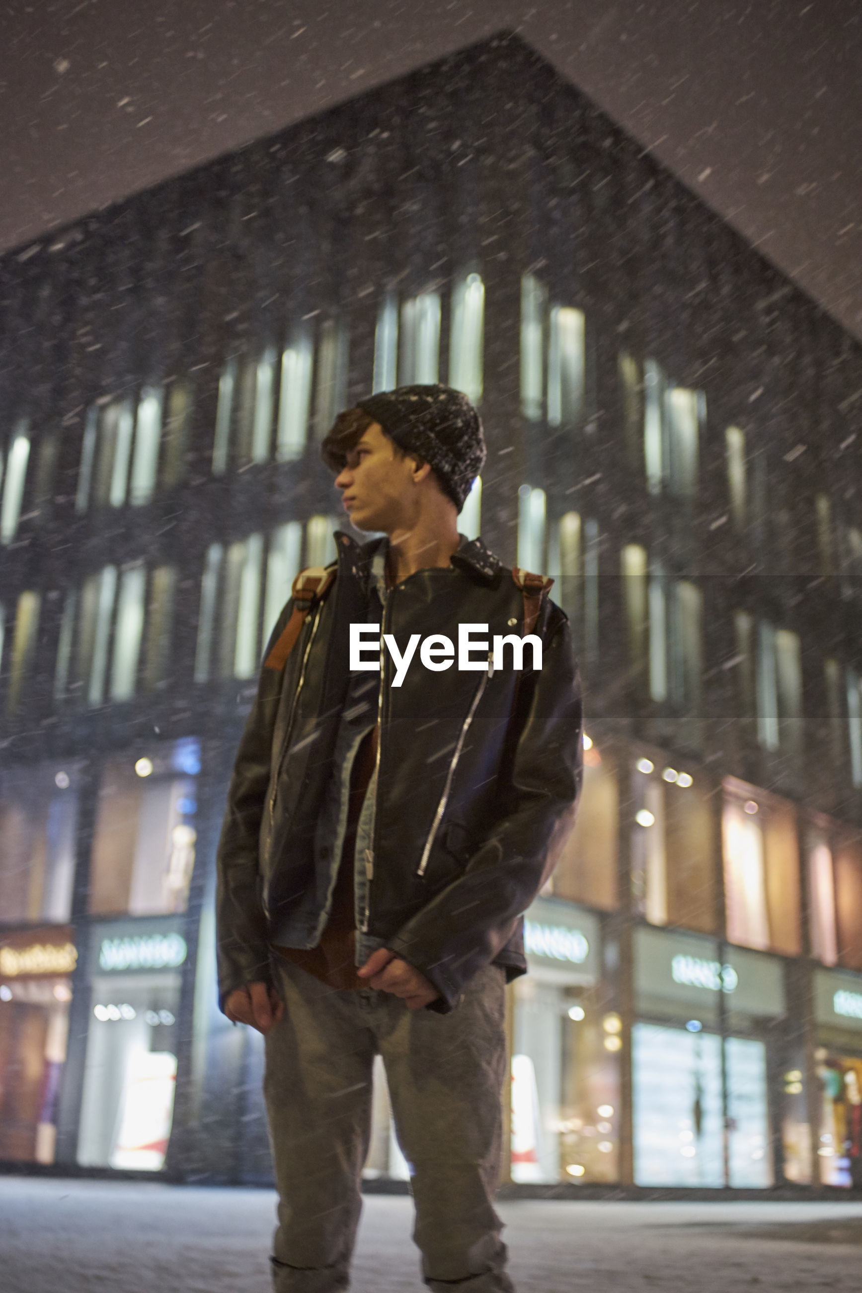 Young man standing in city at night during snowfall