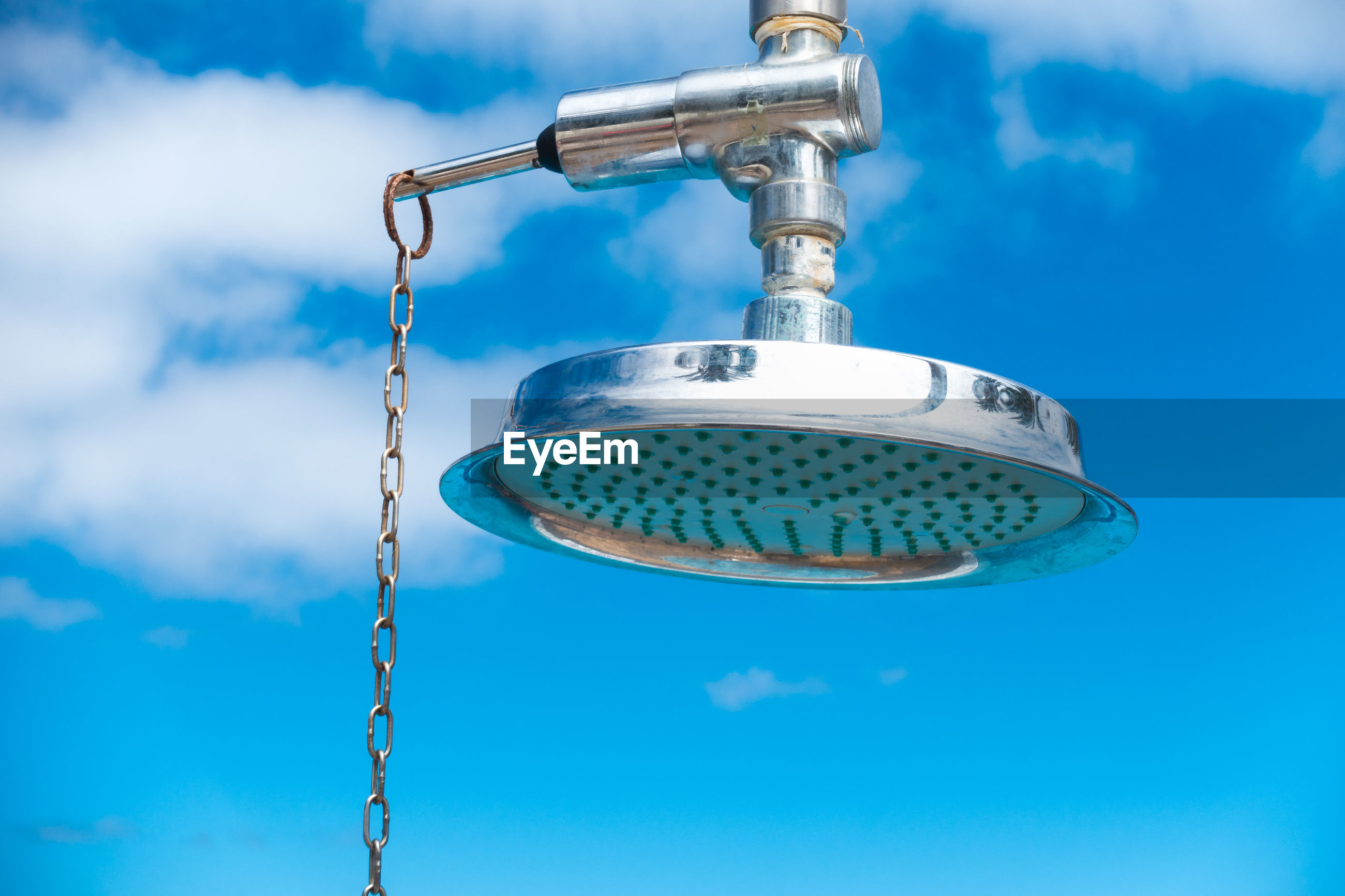 Low angle view of shower head against blue sky