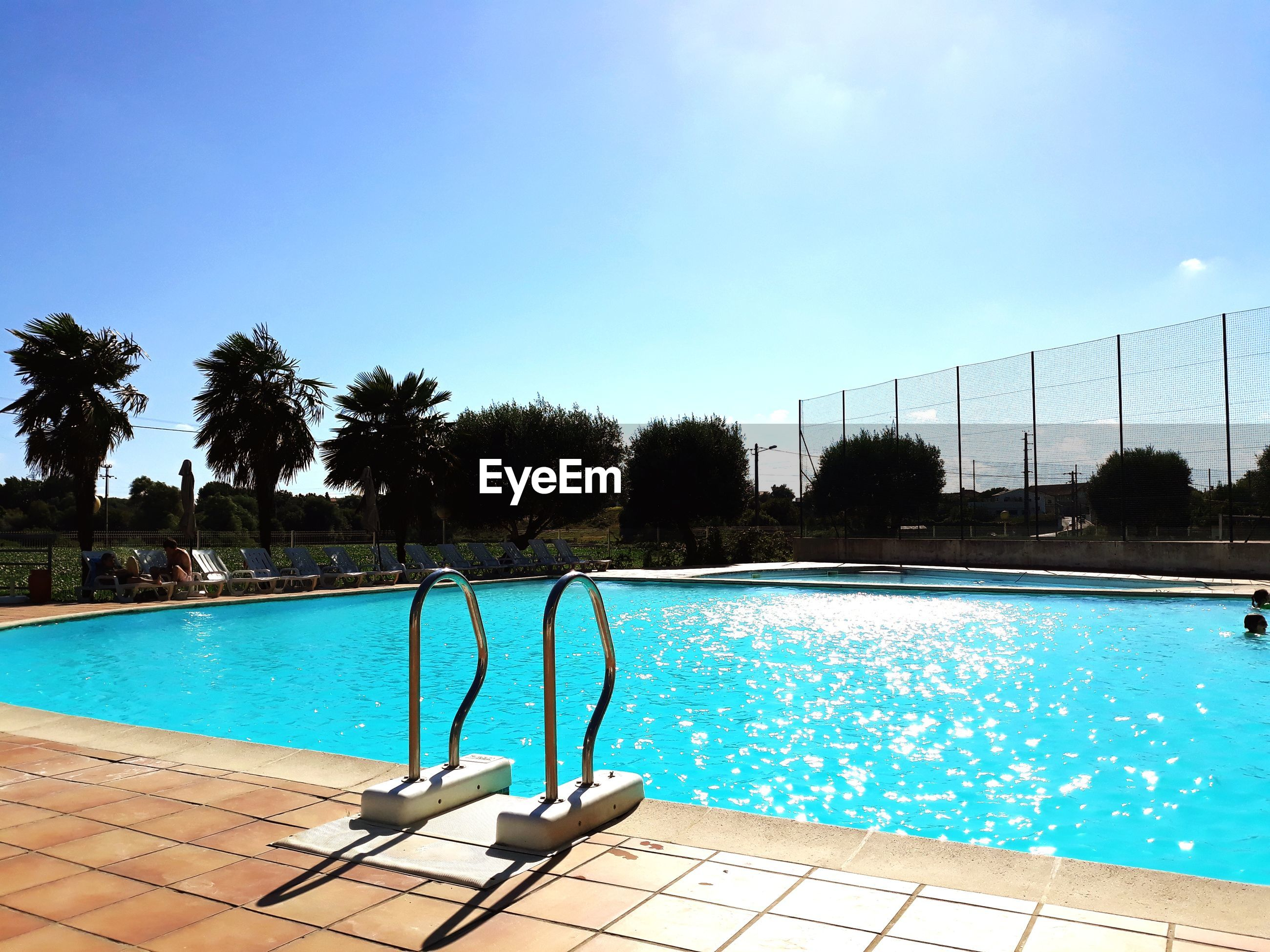 Swimming pool against clear blue sky during sunny day
