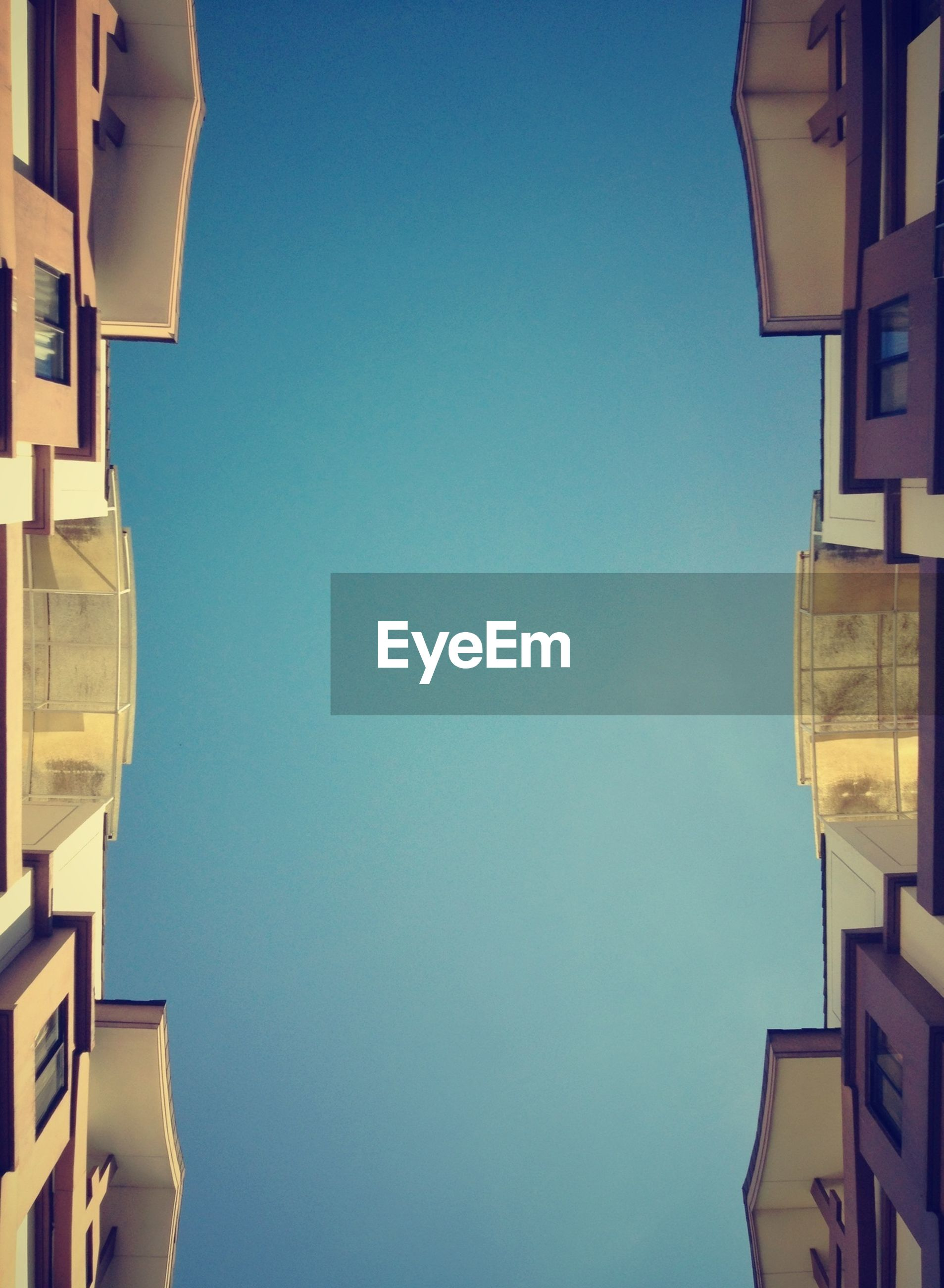 building exterior, architecture, clear sky, built structure, copy space, blue, low angle view, building, city, residential structure, residential building, house, high section, outdoors, no people, part of, day, window, cropped, sky