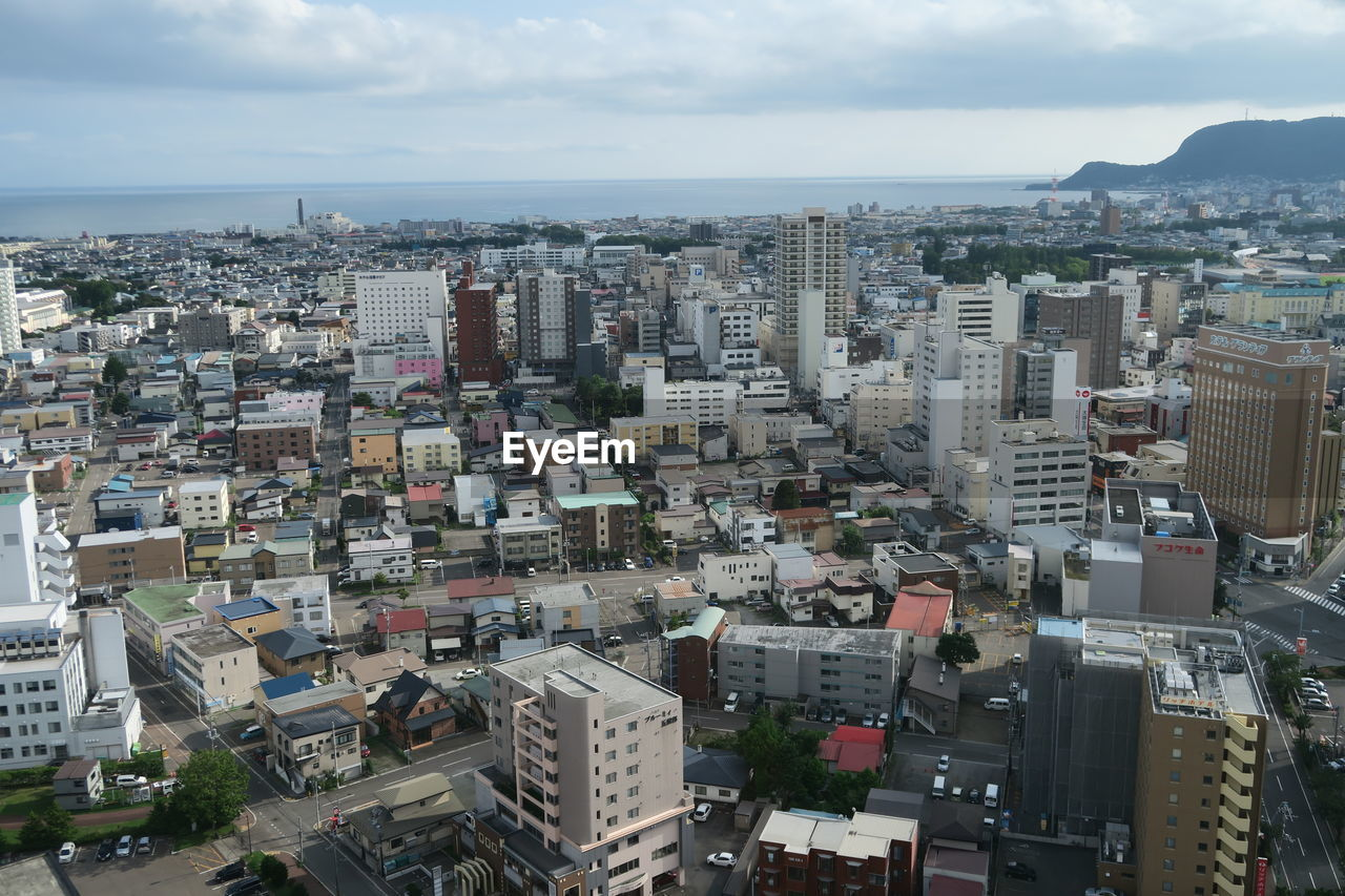 building exterior, architecture, built structure, city, cityscape, sky, building, residential district, crowd, crowded, high angle view, day, cloud - sky, nature, outdoors, horizon, aerial view, sea, office building exterior, skyscraper, settlement, apartment