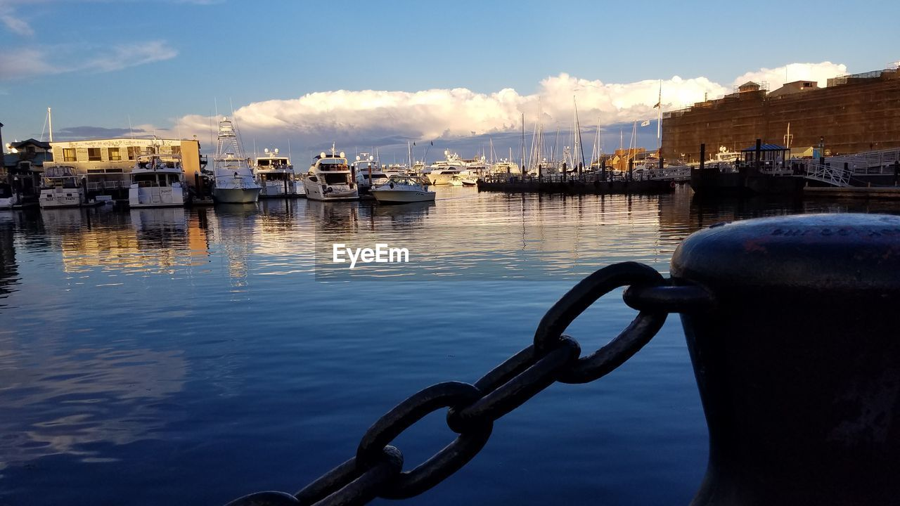 water, mode of transportation, transportation, sky, nautical vessel, cloud - sky, no people, nature, harbor, moored, architecture, built structure, sea, waterfront, chain, day, building exterior, outdoors, reflection, sailboat, marina