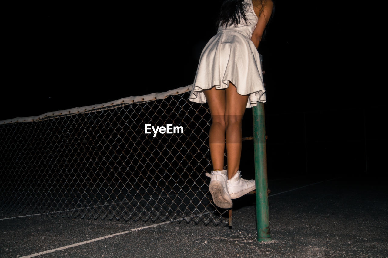 Low Section Of Girl Standing On Fence Over Field At Night