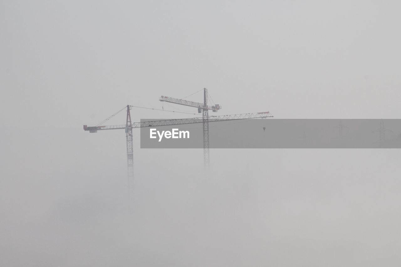 fog, no people, nature, sky, copy space, machinery, built structure, outdoors, architecture, construction site, construction industry, crane - construction machinery, day, winter, cold temperature, industry, connection, fuel and power generation