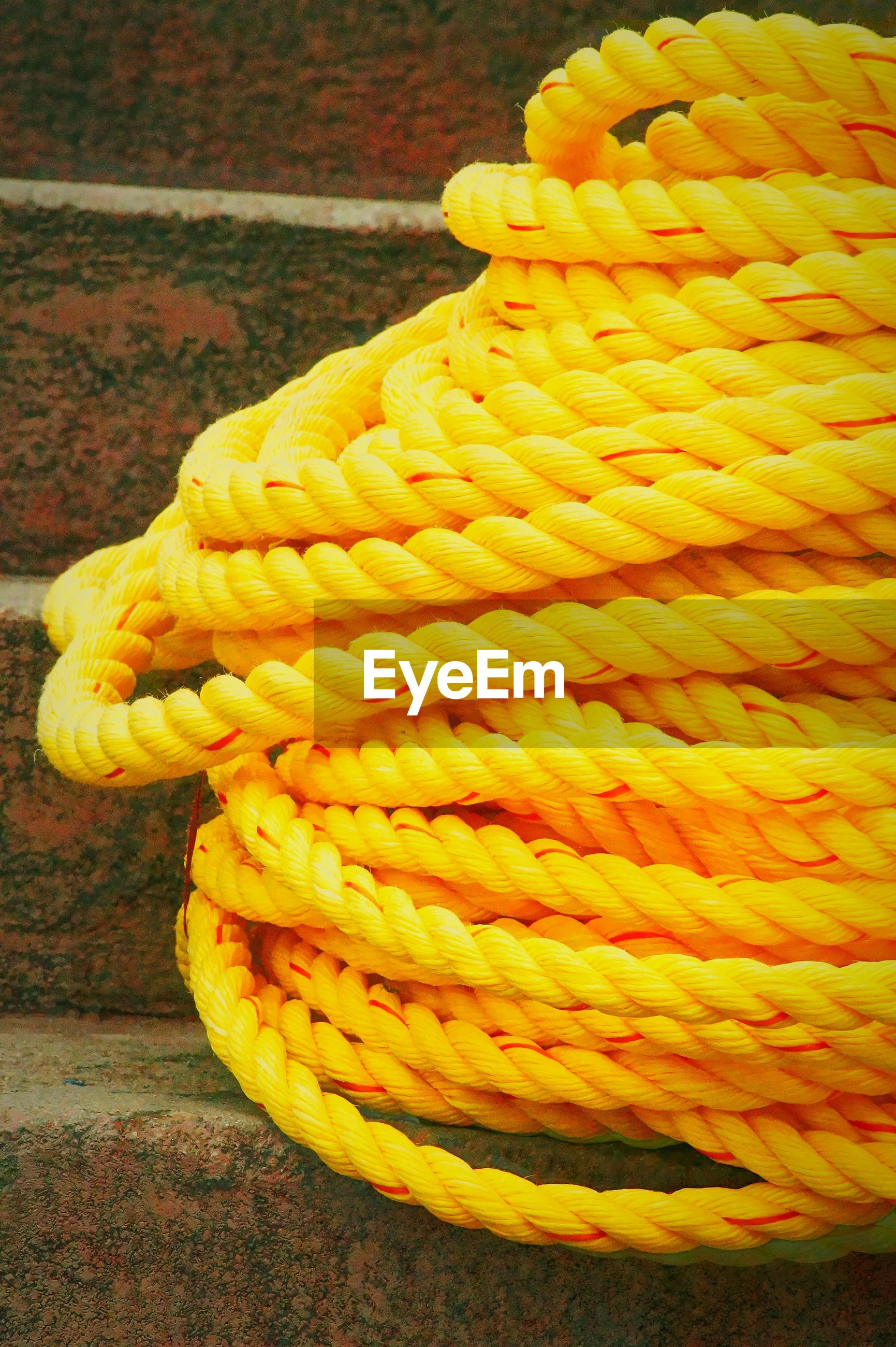 Close-up of yellow coiled rope on steps