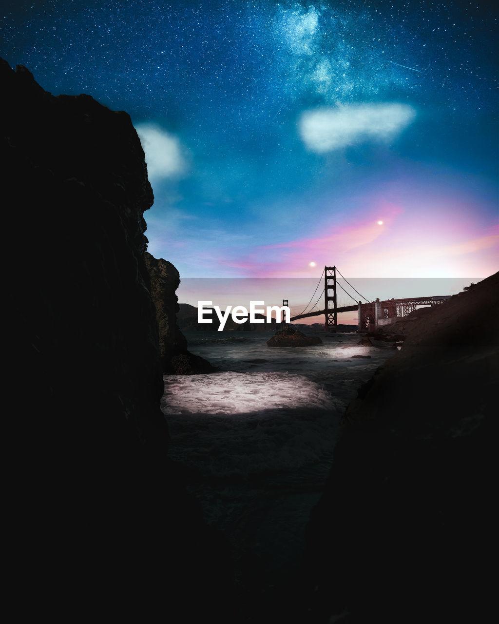 Silhouette Bridge Over Sea Against Sky At Night