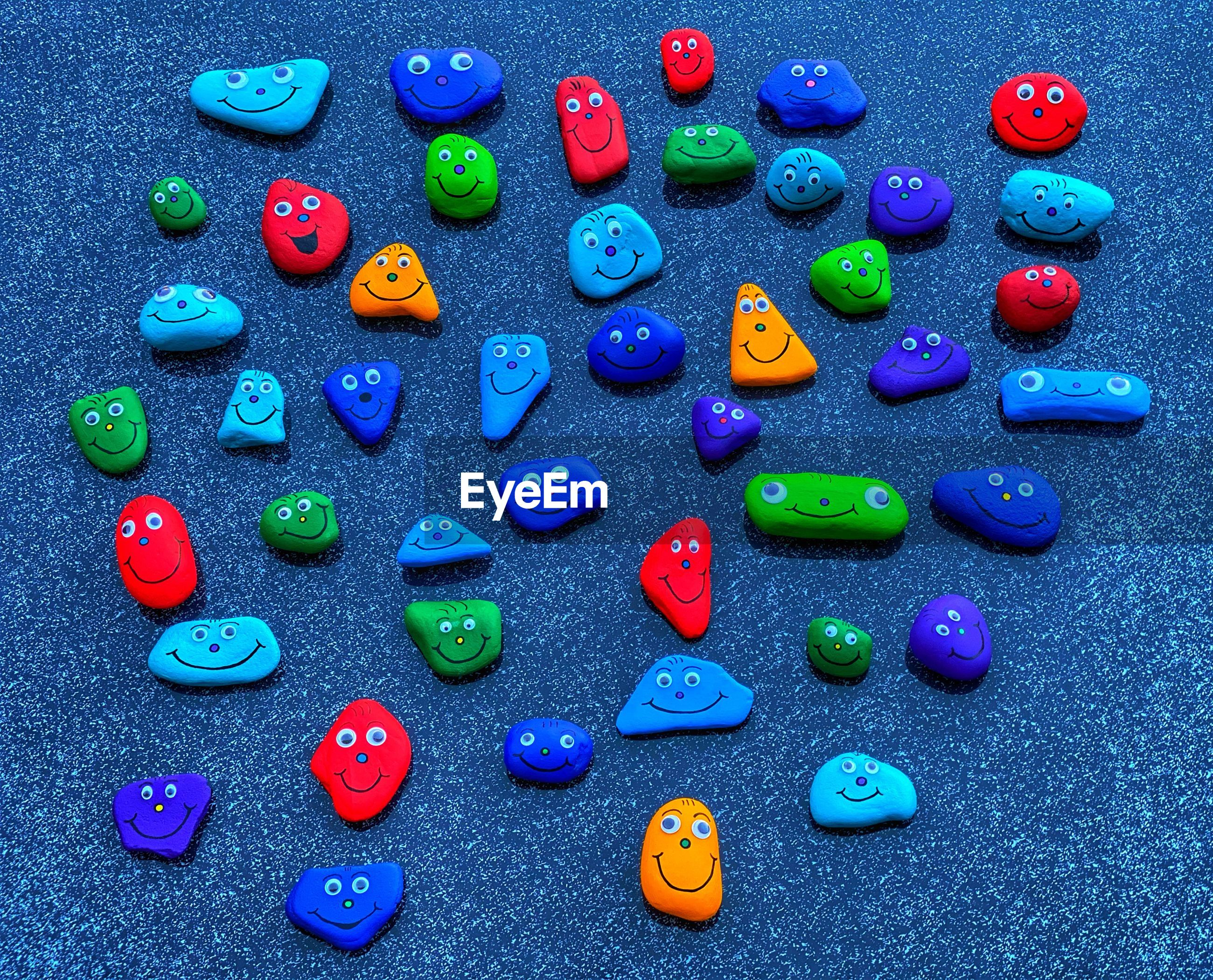 HIGH ANGLE VIEW OF MULTI COLORED PEBBLES ON BLUE