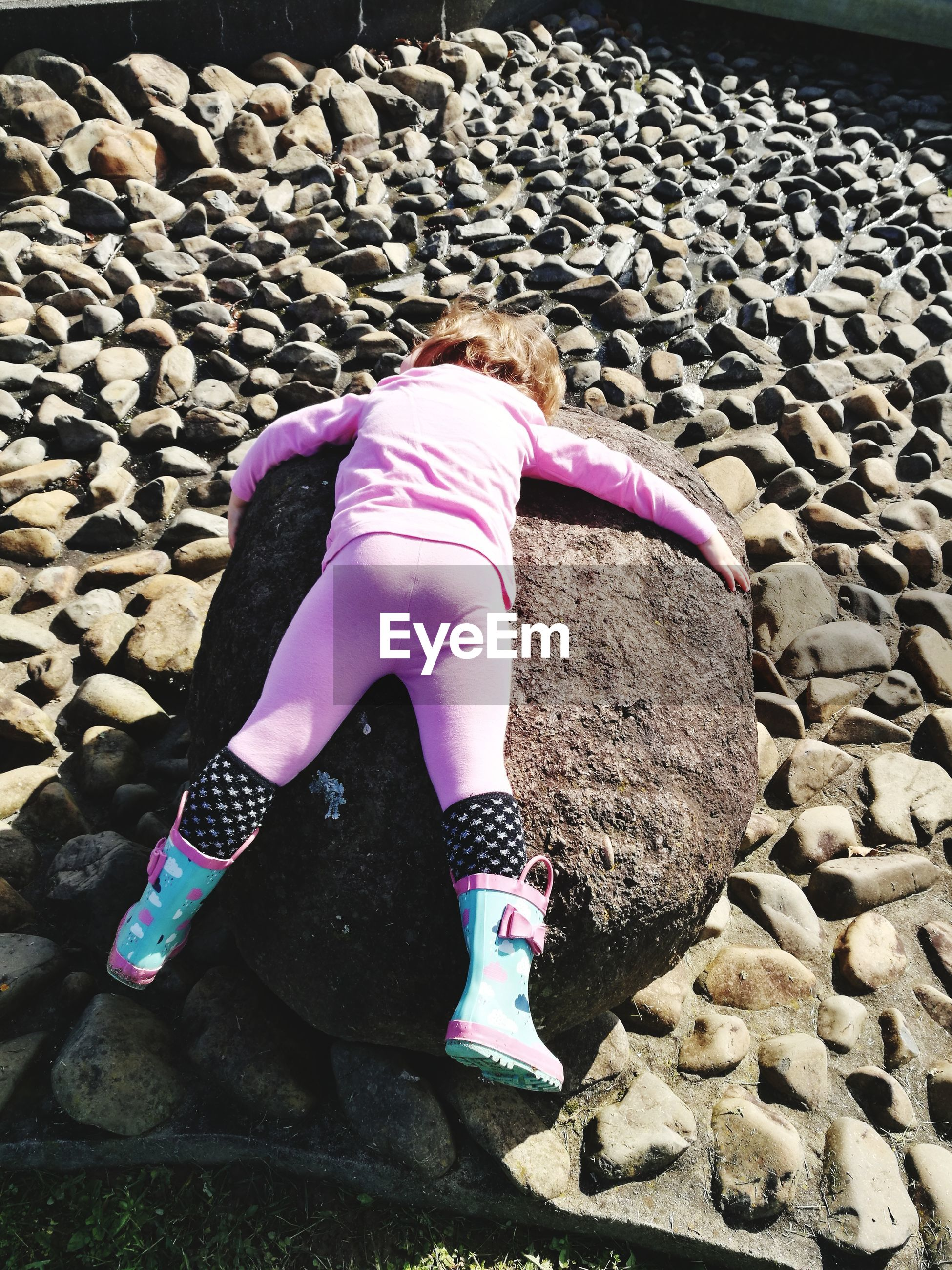 High angle view of girl lying on rock at beach