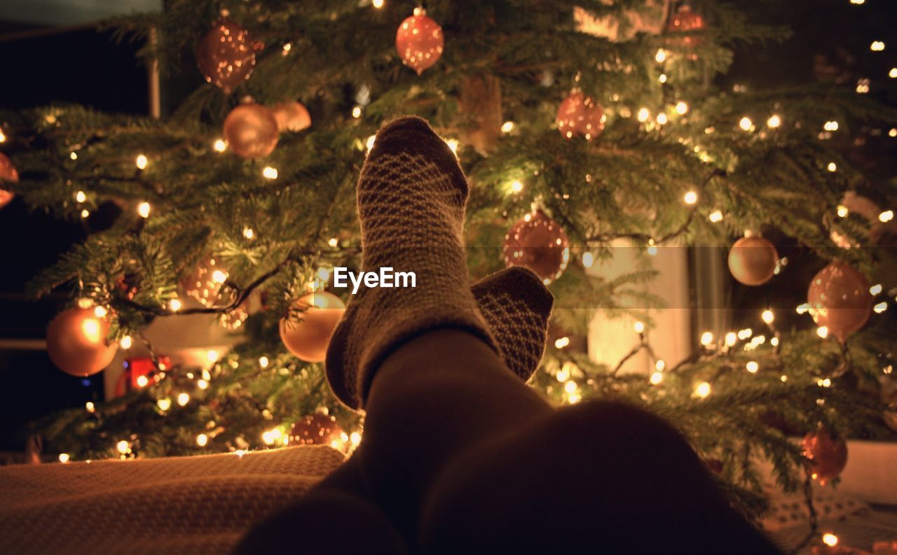 Low Section Of Person Relaxing In Front Of Illuminated Christmas Tree