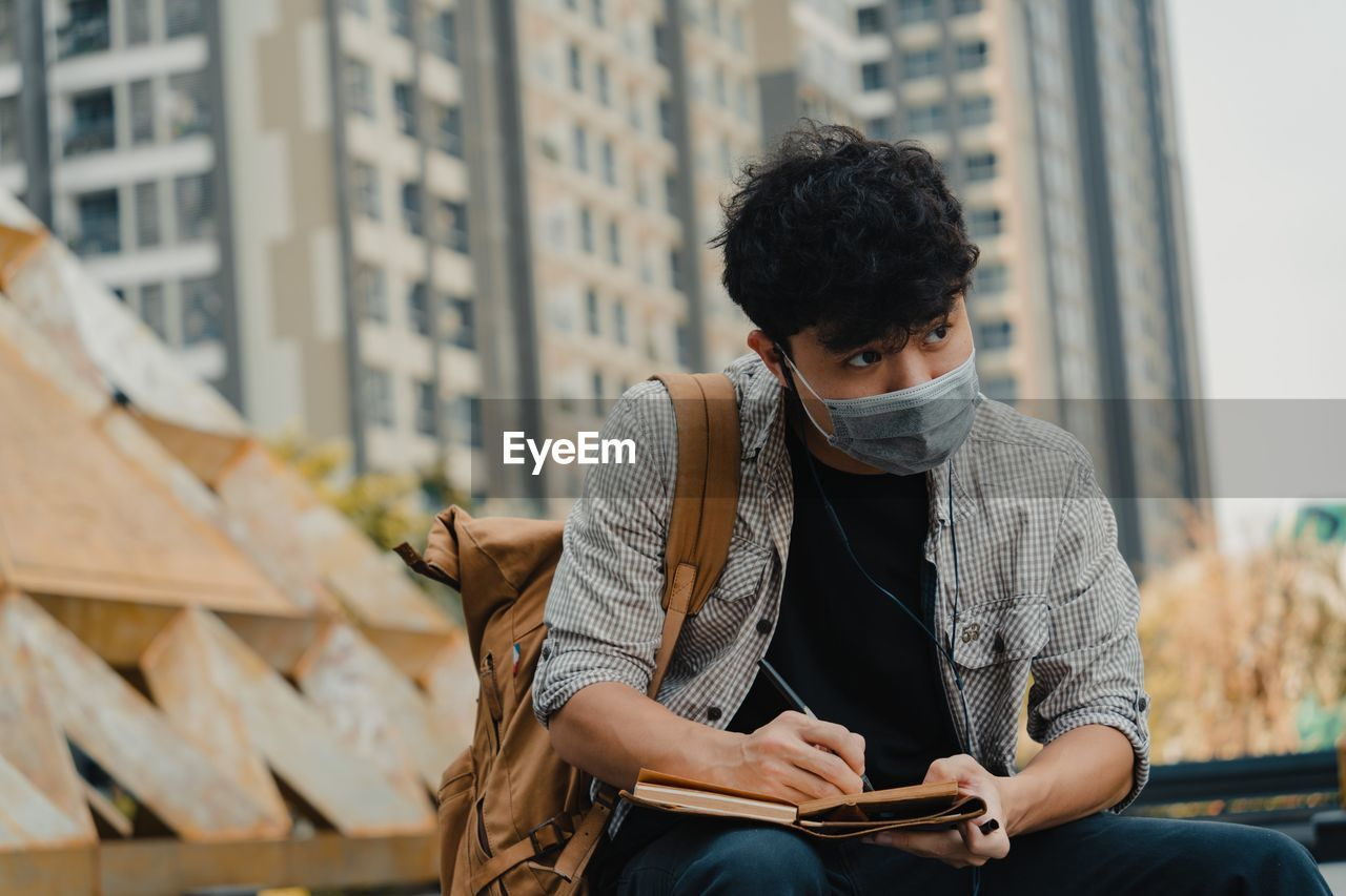 Young man wearing mask writing on diary