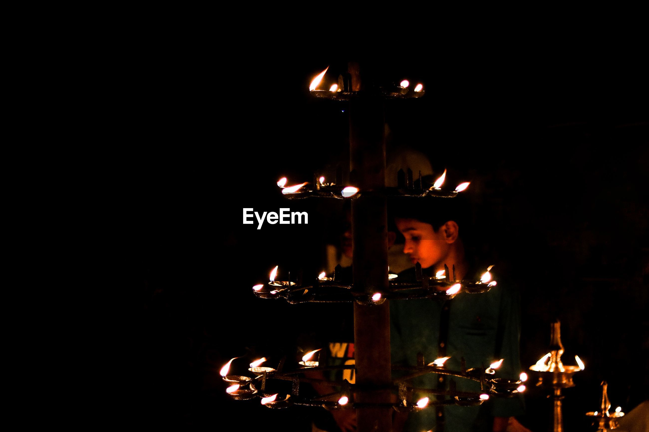 Boy standing by illuminated diyas at night