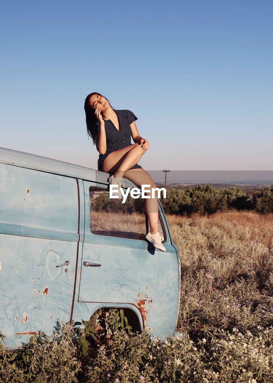 Full Length Of Woman Sitting On Abandoned Van At Field Against Clear Sky