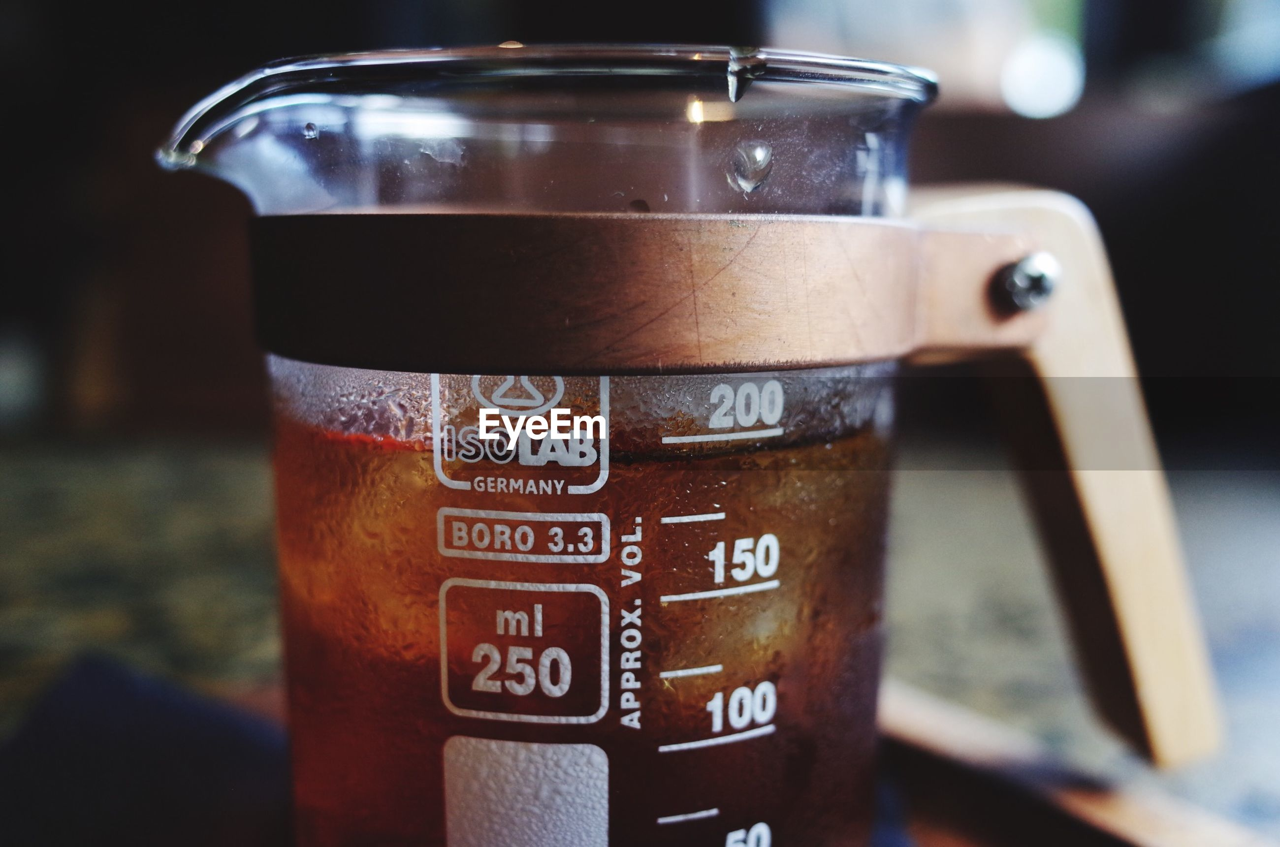close-up, focus on foreground, indoors, text, western script, metal, communication, still life, selective focus, drink, food and drink, no people, container, refreshment, glass - material, table, metallic, number, day, technology