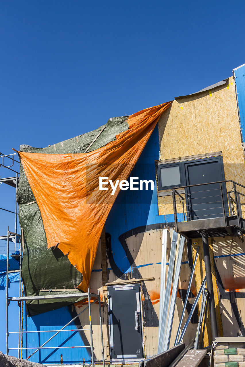 Low angle view of tarpaulin on under construction building against clear blue sky