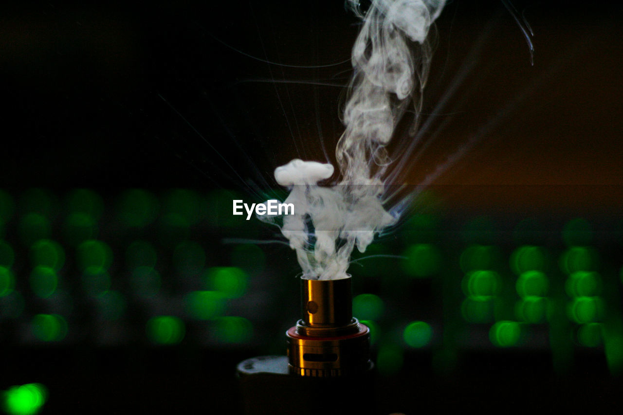 Close-Up Of Electronic Cigarettes Against Green Defocused Lights Against Black Background