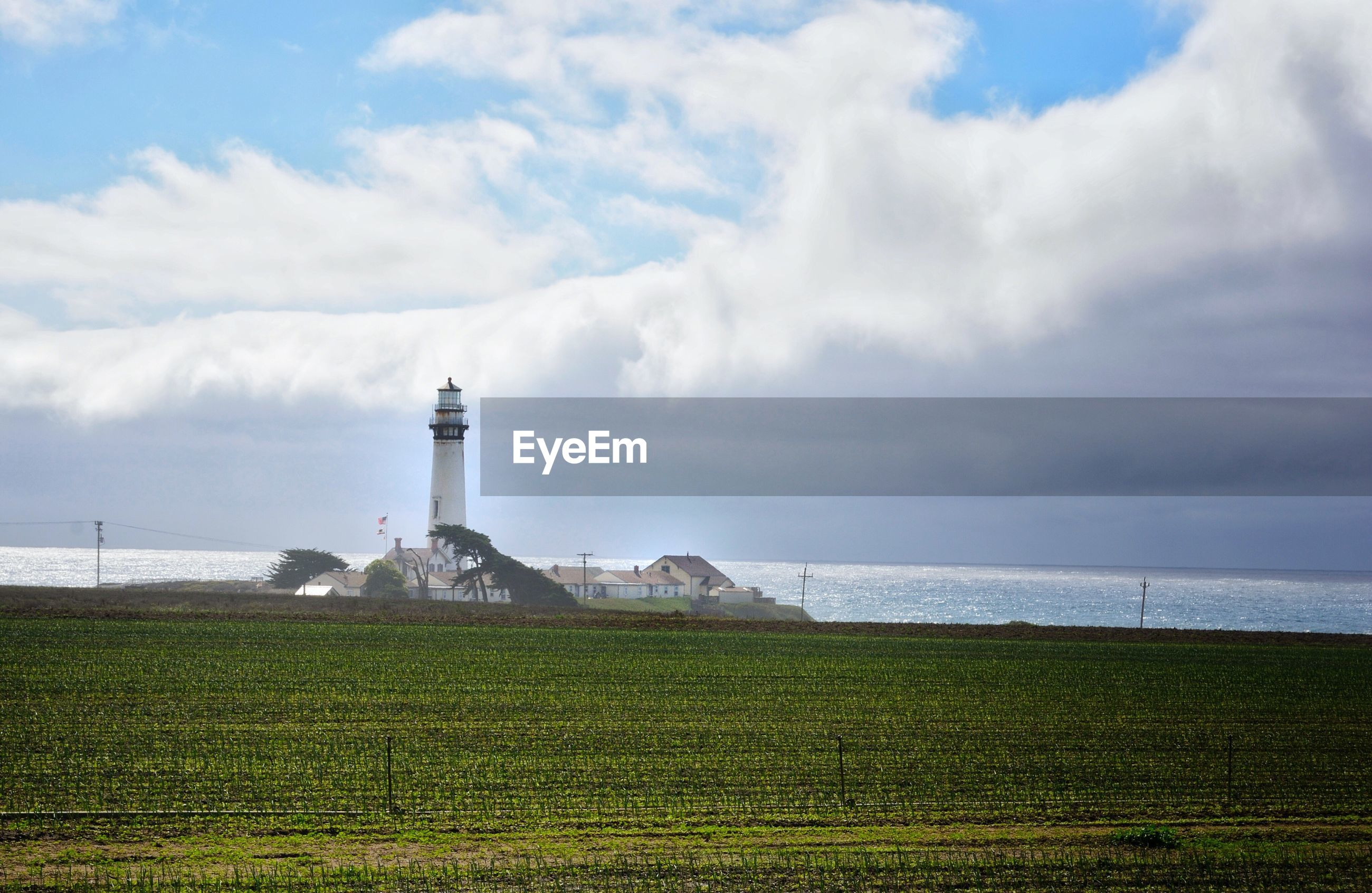 Agricultural field by pigeon point lighthouse against cloudy sky
