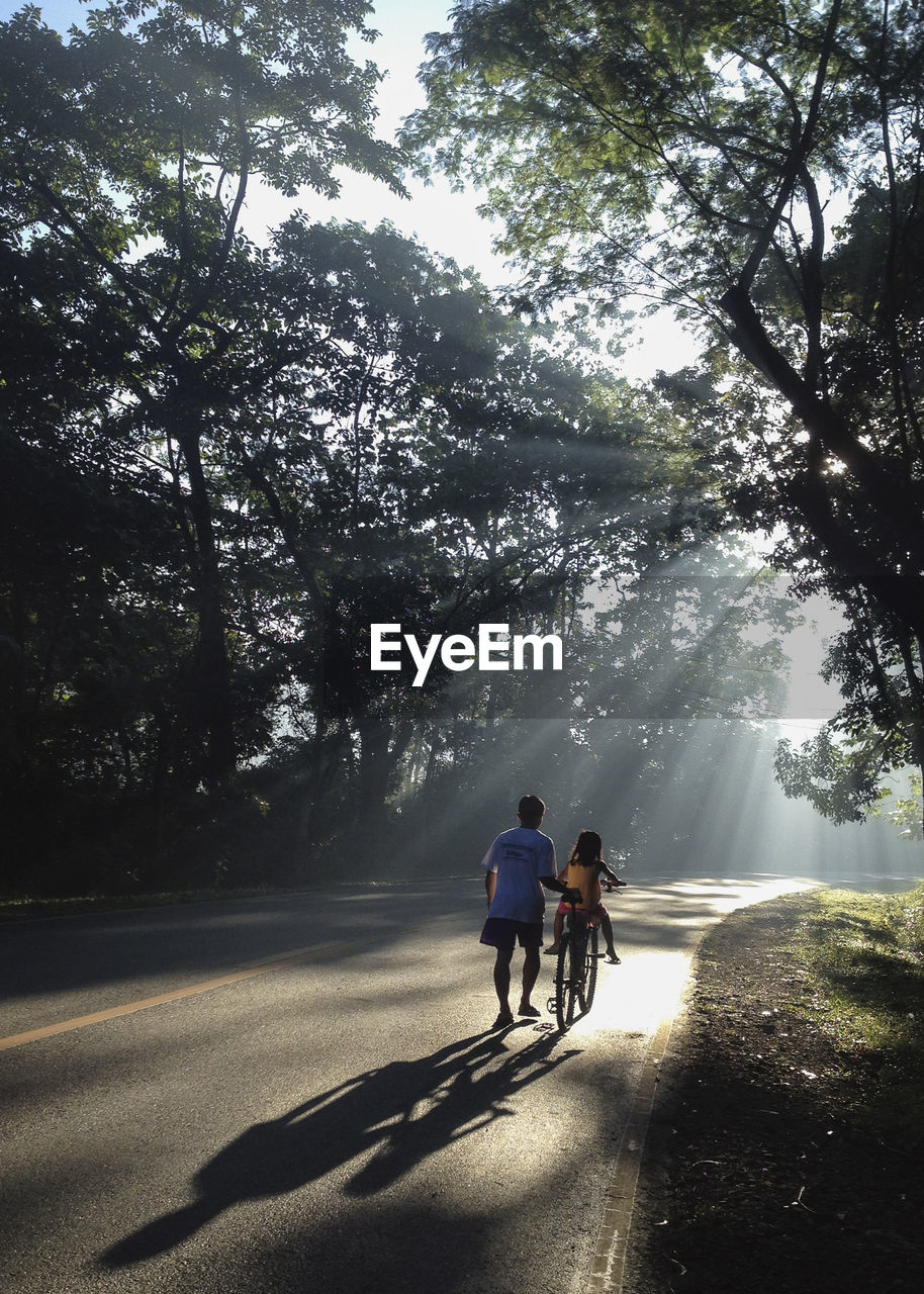 Man Teaching Girl Riding Bicycle On Street Amidst Trees During Sunny Day