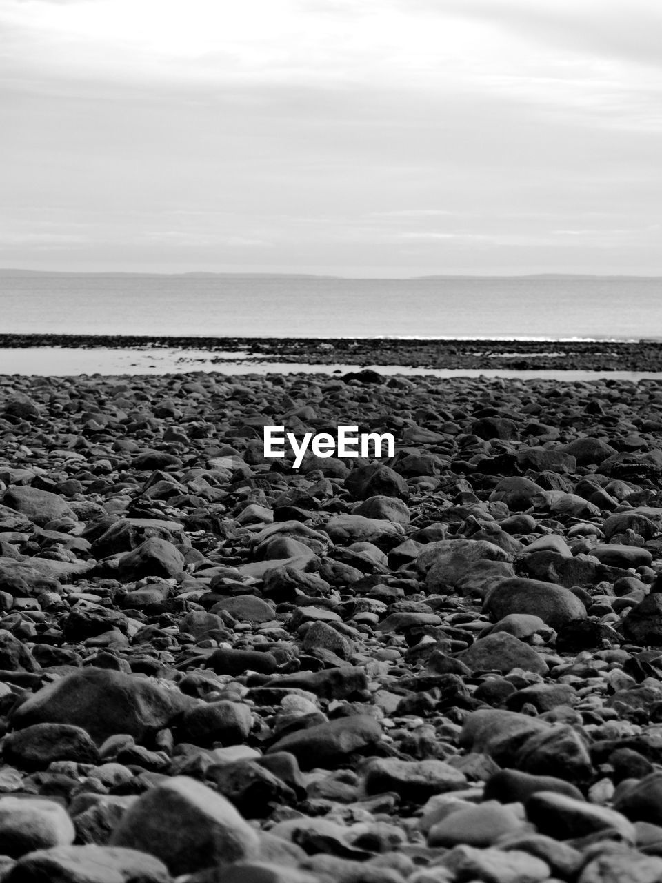 sky, sea, water, scenics - nature, horizon, horizon over water, tranquil scene, land, beauty in nature, tranquility, nature, beach, pebble, rock, no people, stone, day, solid, cloud - sky, surface level, outdoors, gravel, rocky coastline