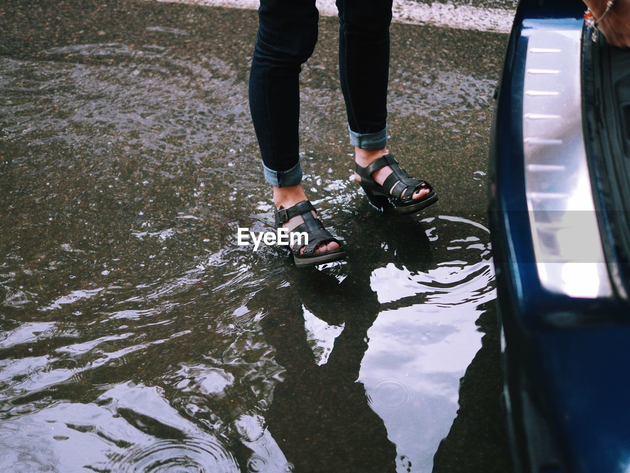 Low Section Of Woman Standing In Puddle