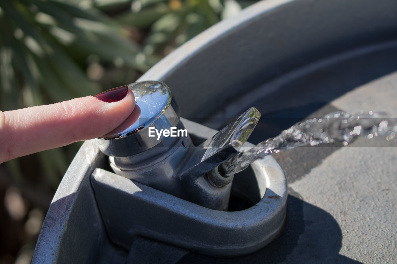 Close-up of woman pressing faucet of drinking fountain