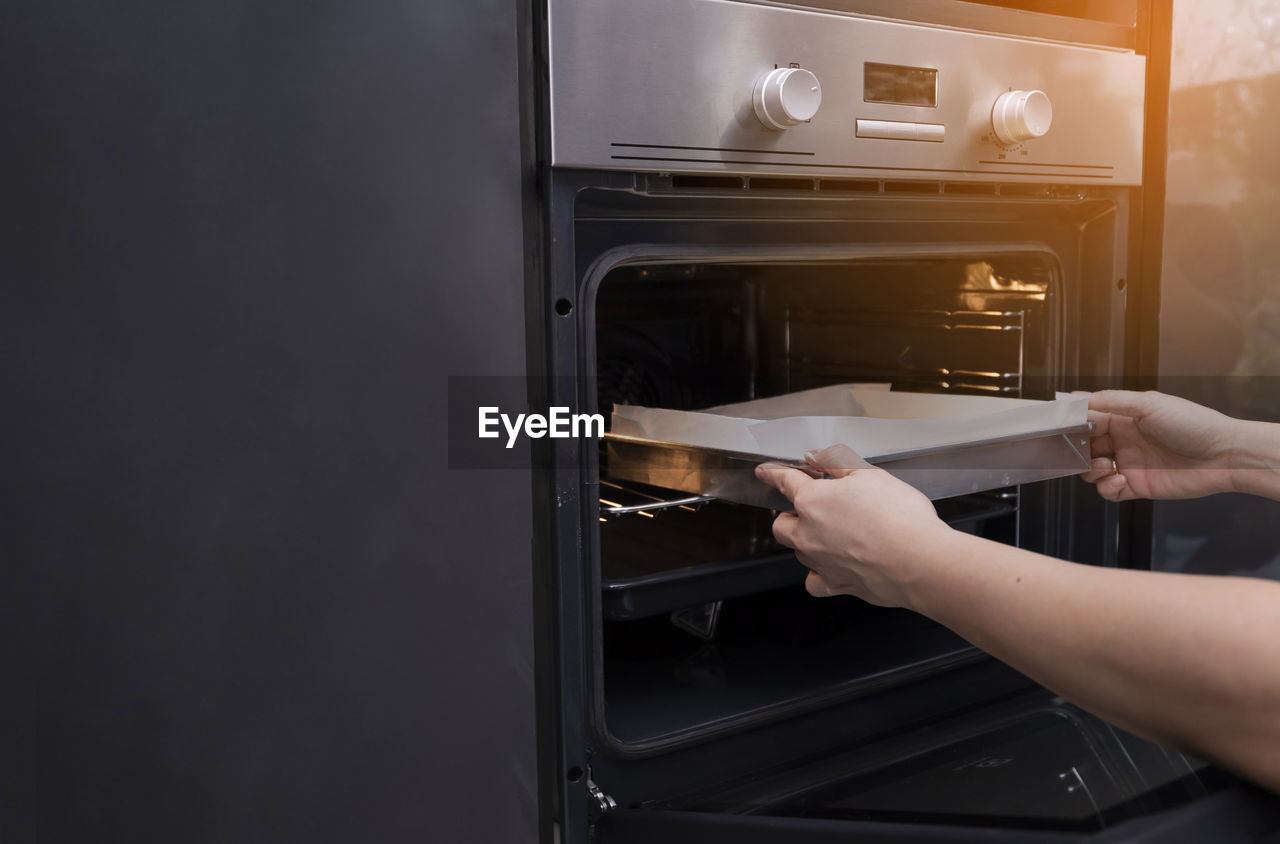 human hand, hand, one person, holding, appliance, indoors, human body part, domestic kitchen, kitchen, real people, home, domestic room, lifestyles, oven, household equipment, domestic life, preparation, removing, refrigerator, preparing food, finger