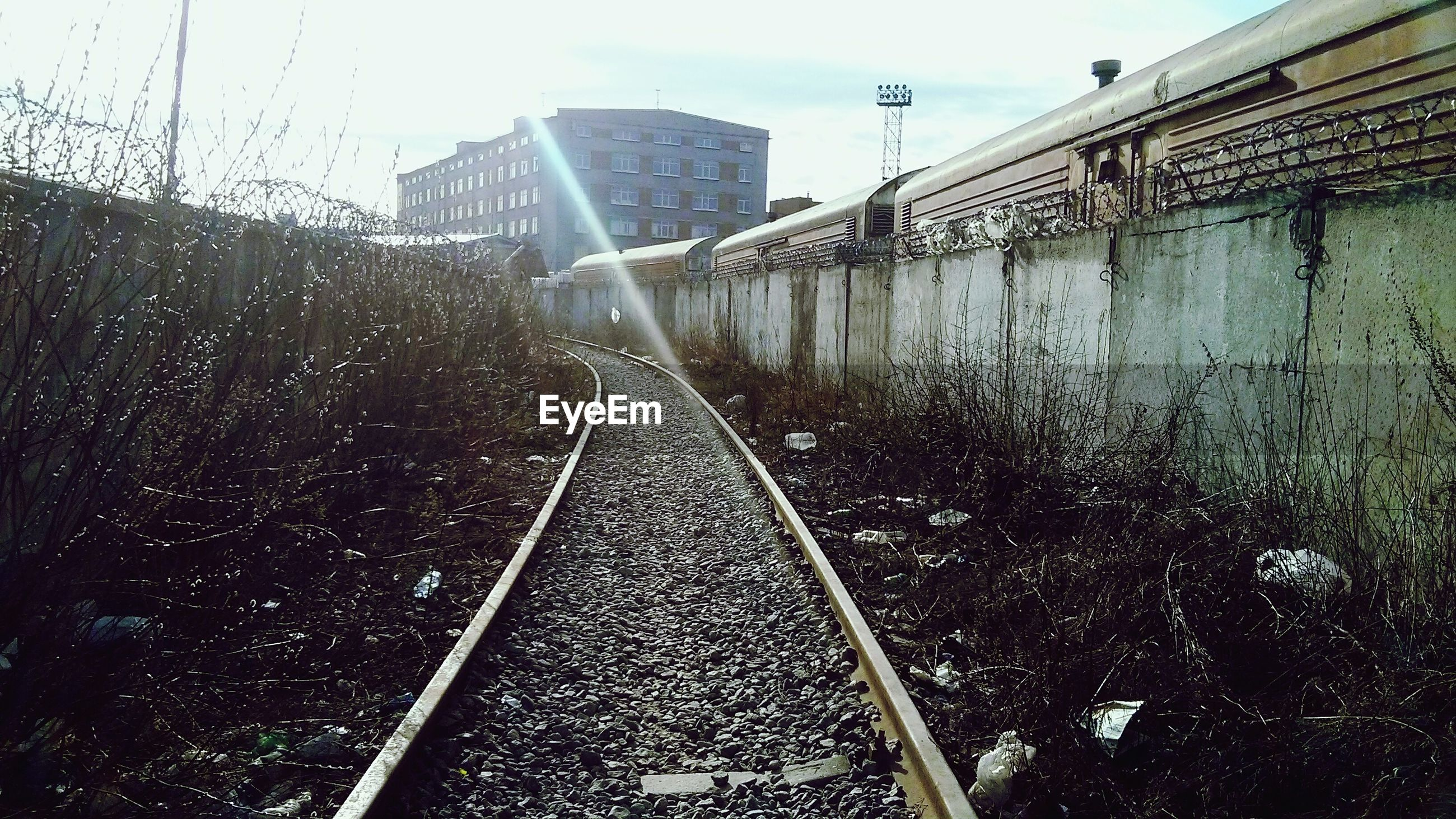 railroad track, transportation, built structure, architecture, rail transportation, connection, the way forward, diminishing perspective, sky, city, building exterior, bridge - man made structure, vanishing point, railway track, public transportation, clear sky, day, water, outdoors, no people