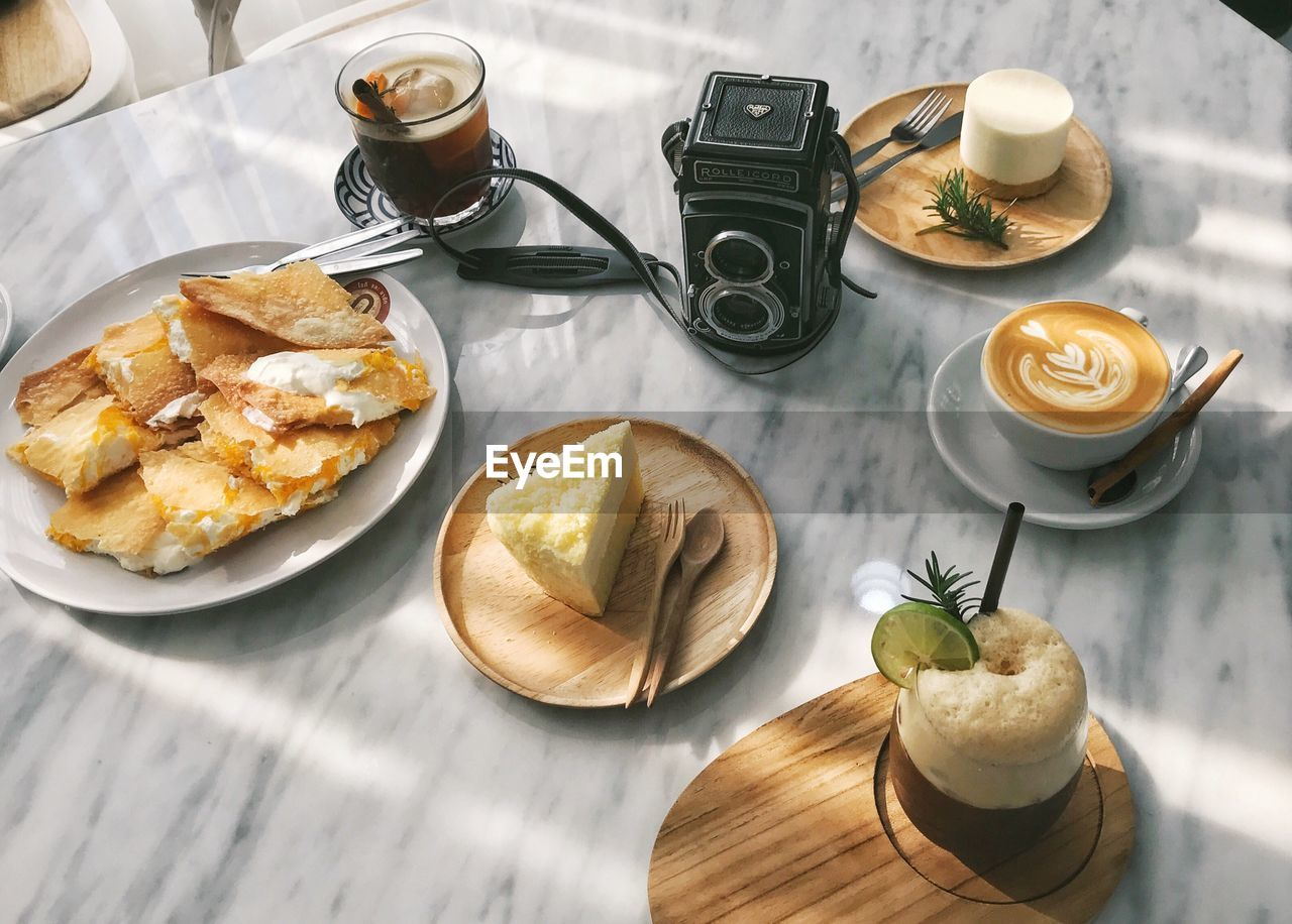 food and drink, drink, refreshment, table, coffee - drink, food, coffee cup, high angle view, plate, freshness, indoors, ready-to-eat, serving size, healthy eating, no people, breakfast, drinking glass, frothy drink, cappuccino, latte, day, sweet food, close-up, froth art