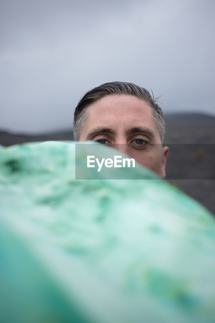 Portrait of man peeking from behind rock