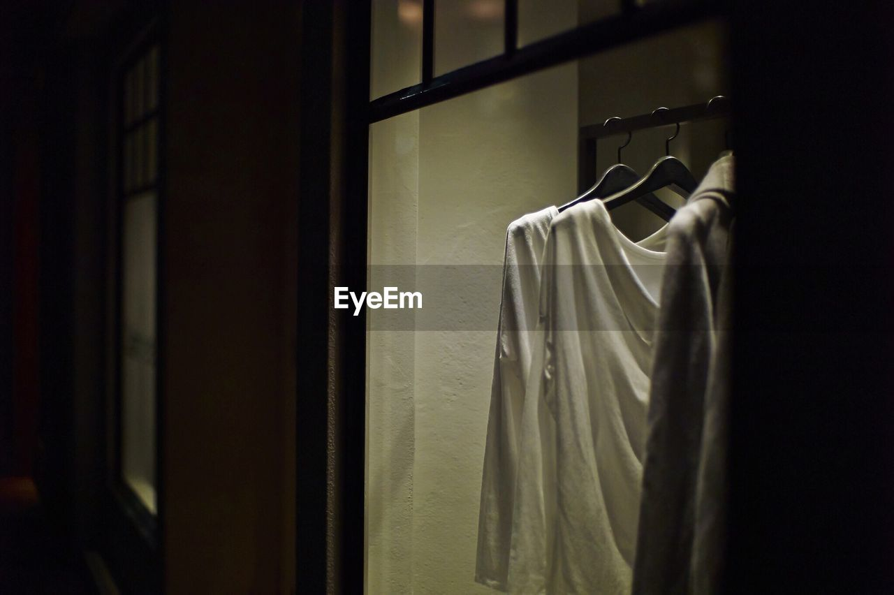 Clothes Hanging On Coathangers Seen Through Glass Window Of Store