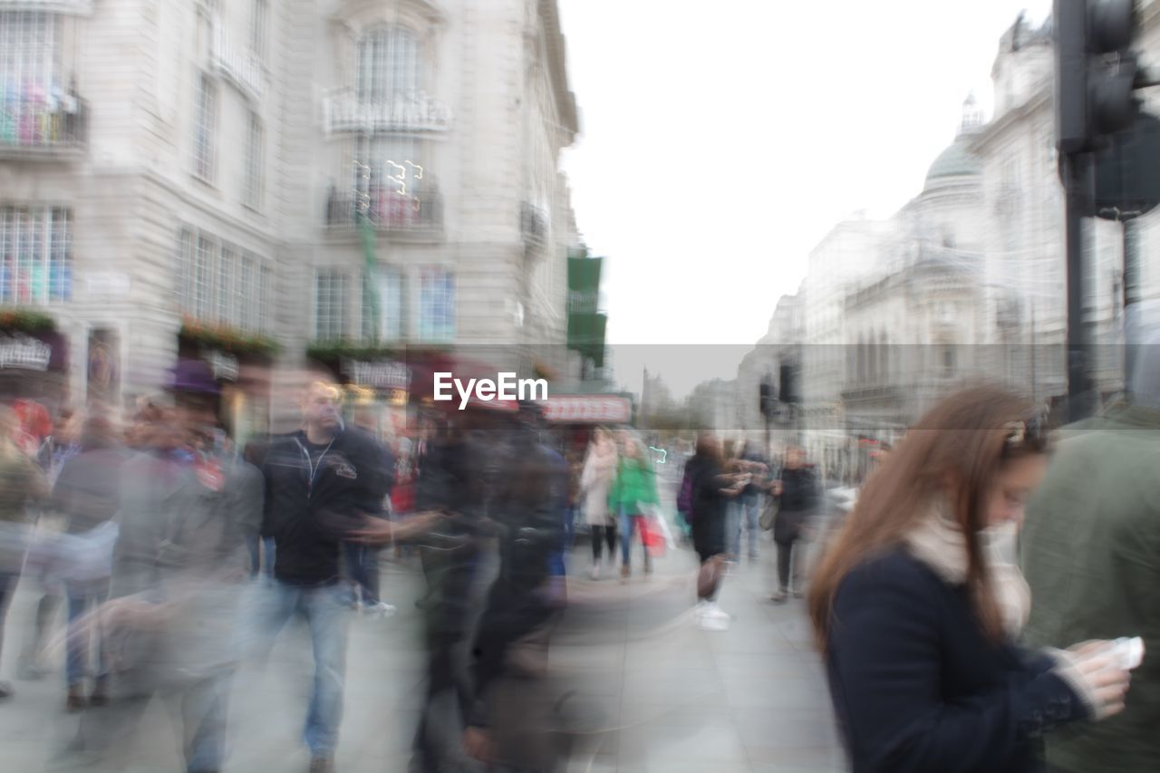 blurred motion, architecture, city, walking, building exterior, street, built structure, large group of people, motion, real people, day, women, group of people, crowd, outdoors, people, adult