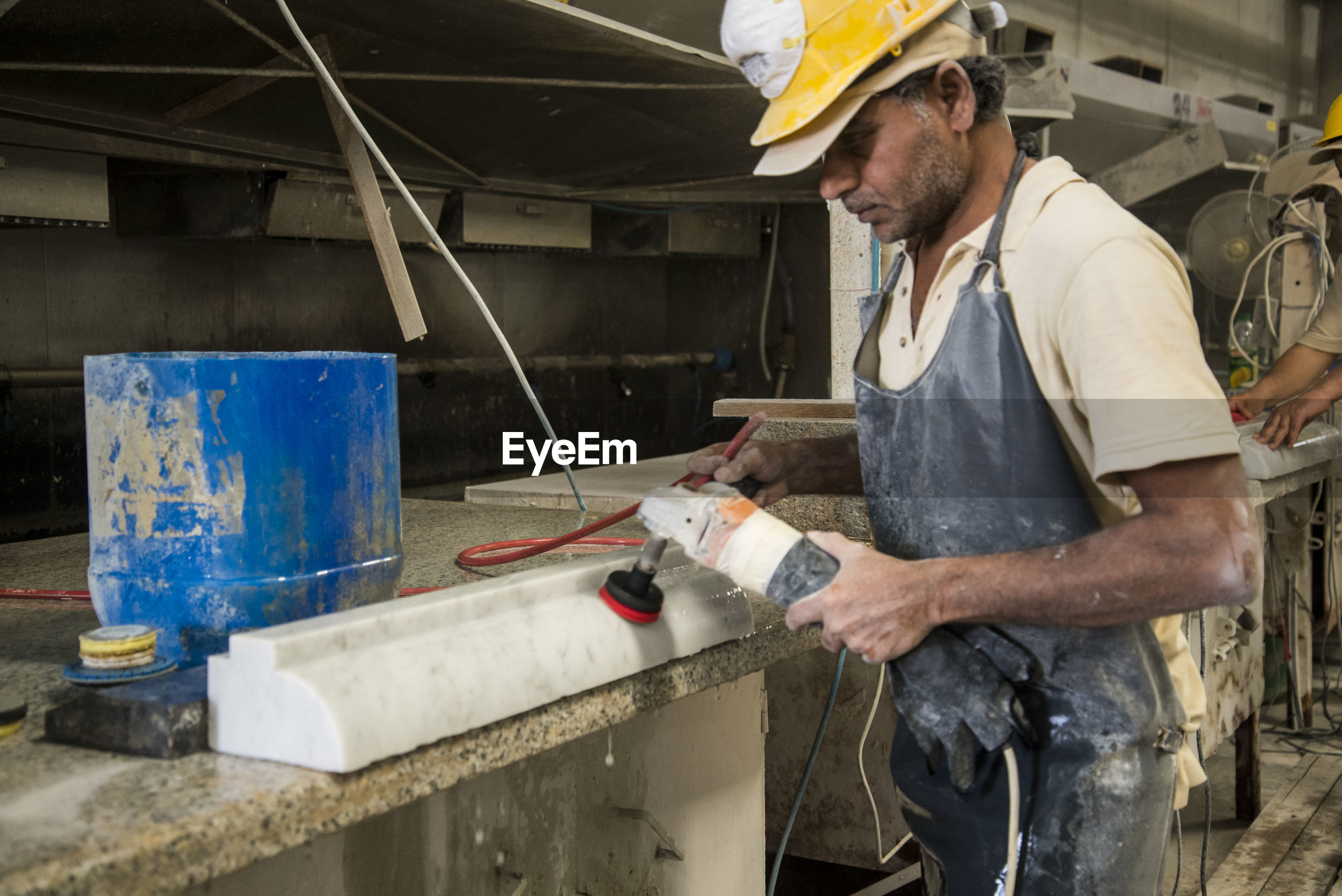 MAN WORKING ON GARBAGE AT WORKSHOP