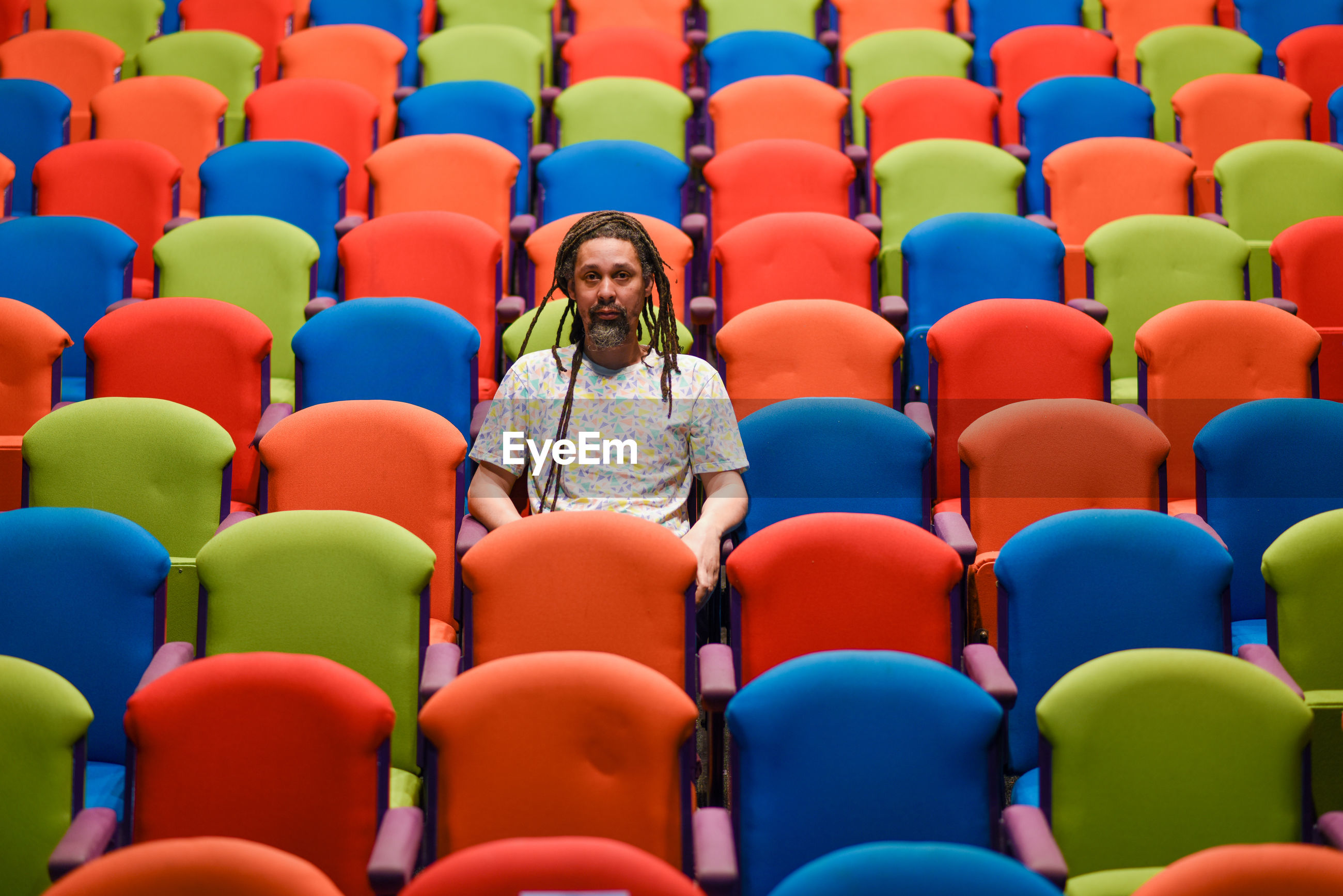 Colorful chairs with one person sitting alone in theatre