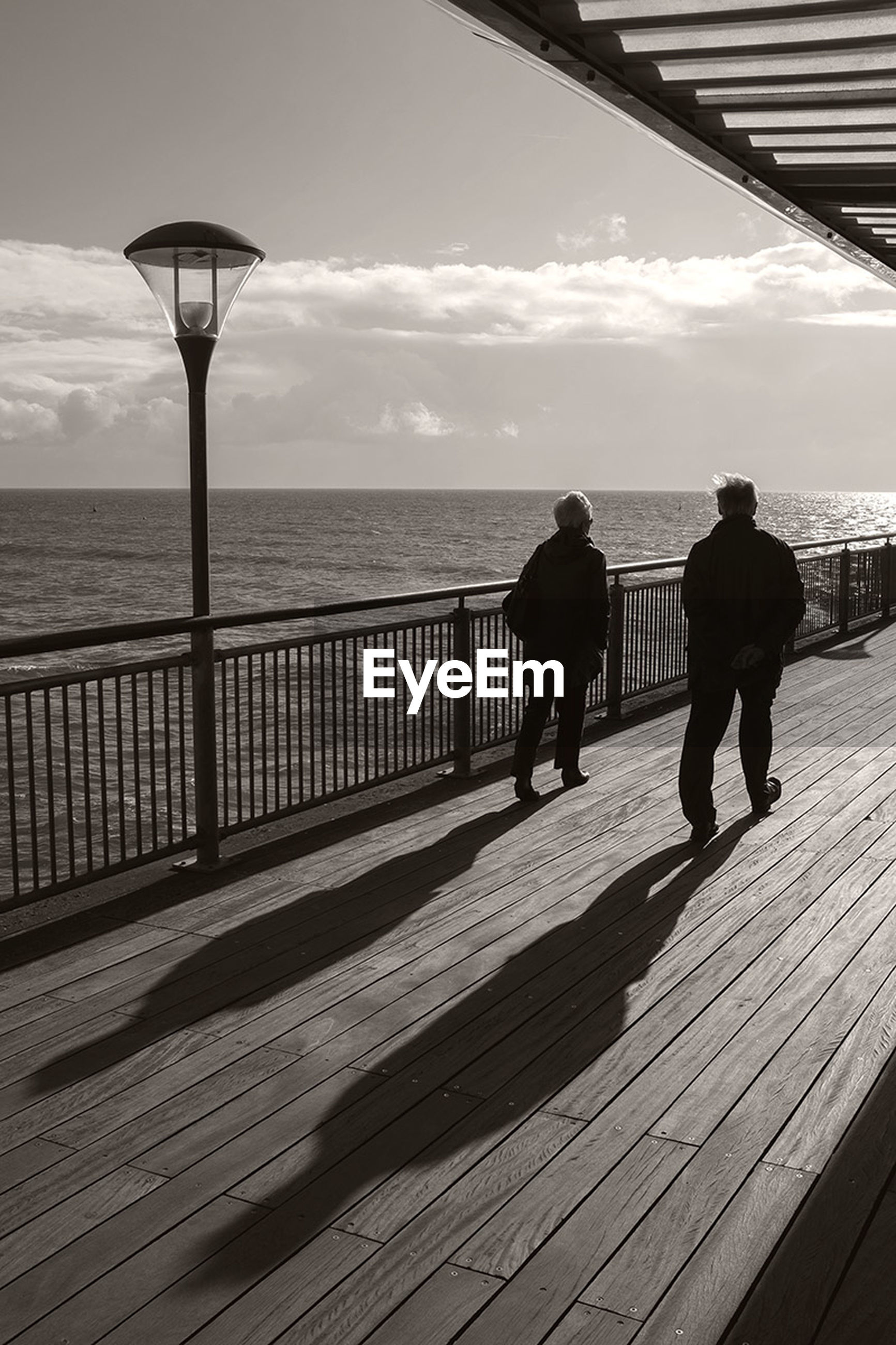 sea, horizon over water, water, sky, full length, railing, men, silhouette, walking, rear view, lifestyles, pier, leisure activity, person, beach, standing, nature