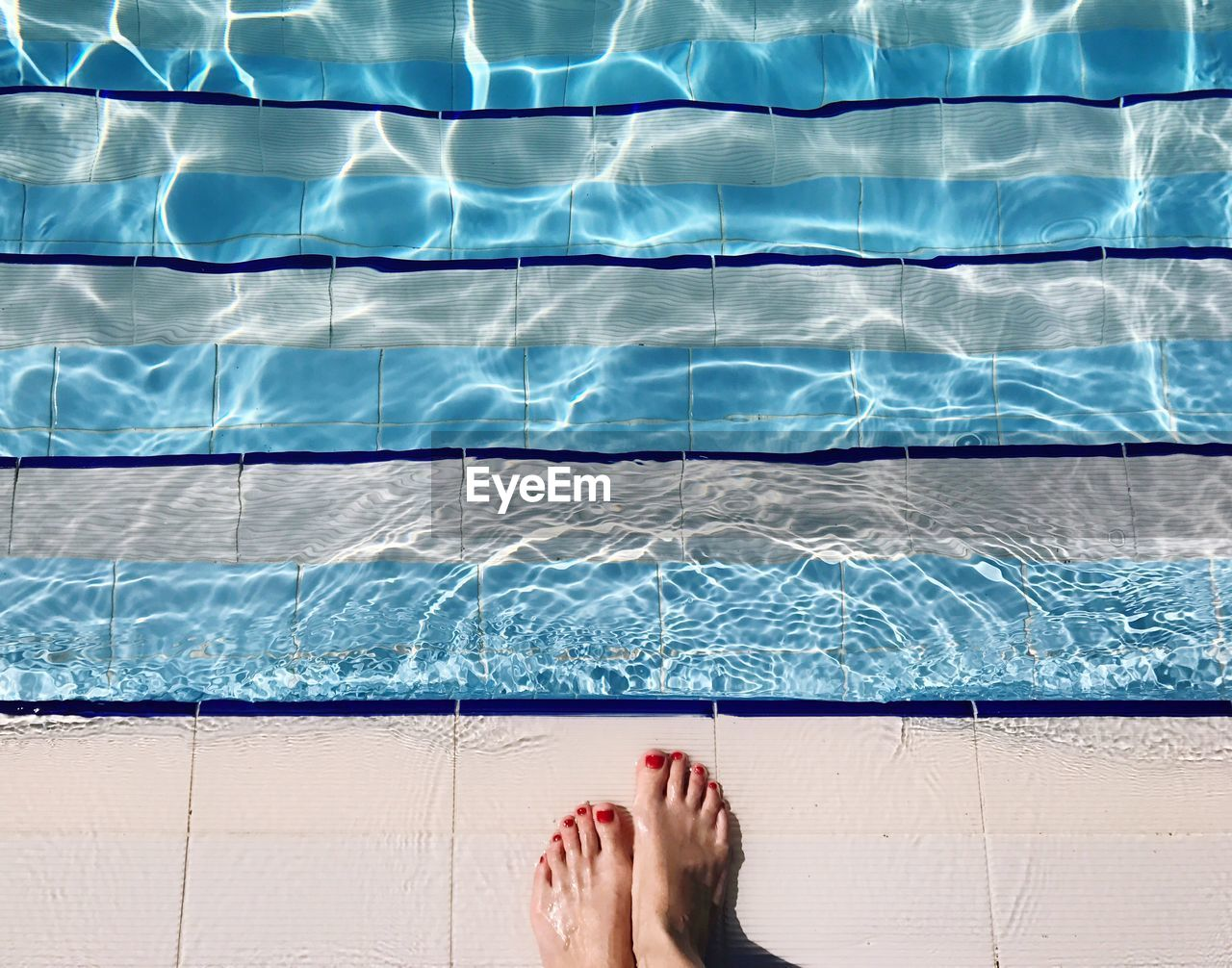 Low Section Of Woman Standing At Poolside During Sunny Day