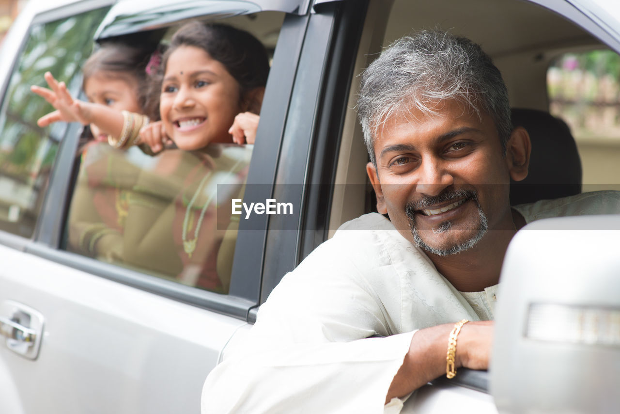 Portrait of smiling father enjoying road trip with daughters seen through car window