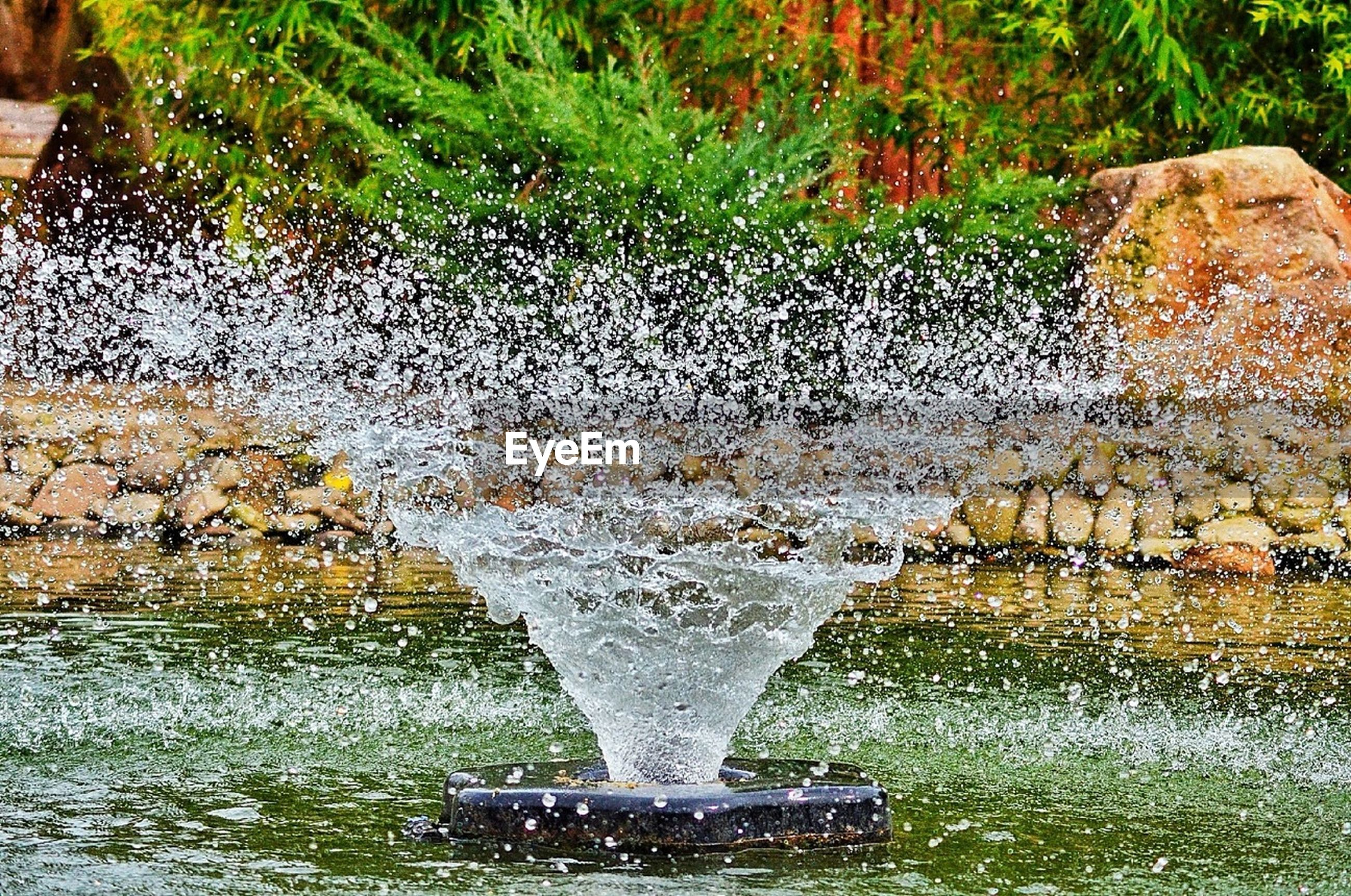water, motion, splashing, fountain, rock - object, flowing, flowing water, waterfront, wet, nature, day, outdoors, long exposure, waterfall, plant, reflection, stone - object, park - man made space, stone material, falling