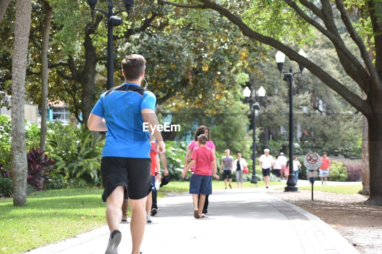 tree, jogging, rear view, running, sports clothing, togetherness, full length, exercising, leisure activity, outdoors, day, lifestyles, real people, healthy lifestyle, park - man made space, sport, nature, men, friendship, people, young adult, adult