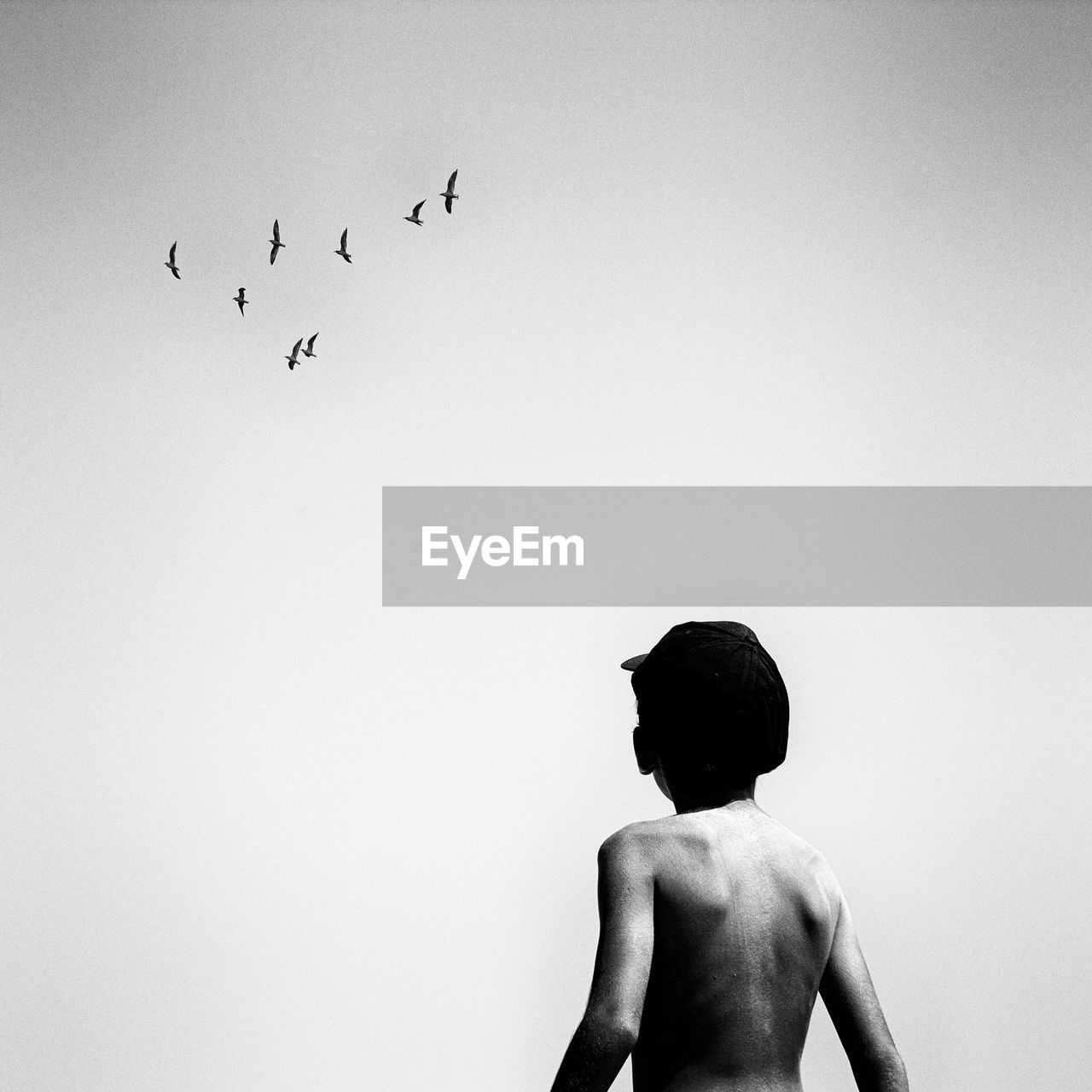 Rear View Of Shirtless Boy Standing Against Clear Sky