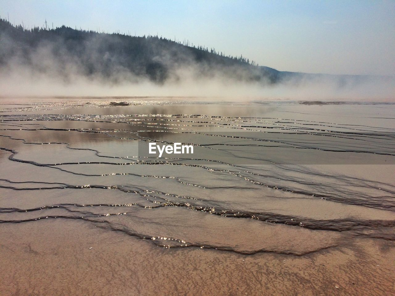 Scenic View Of Smoke Over Grand Prismatic Spring By Mountain